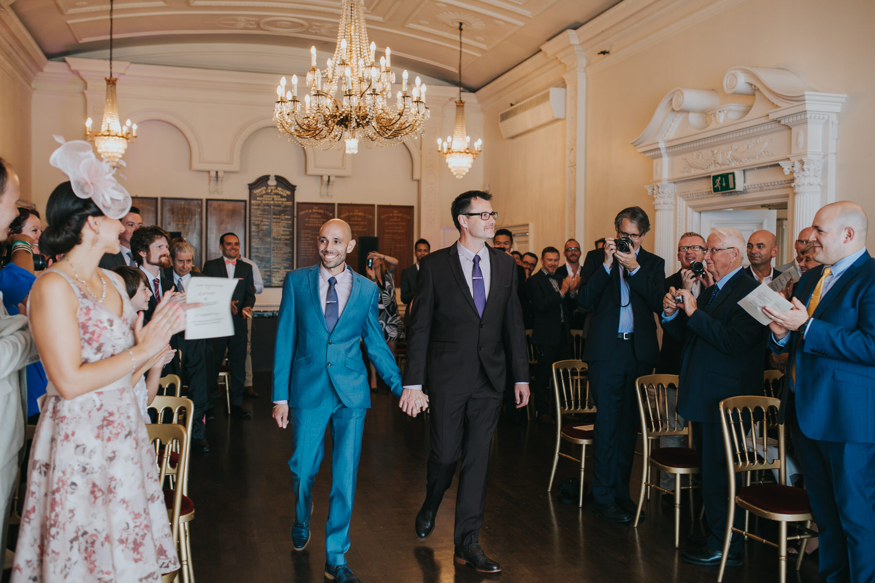 68 two grooms enter same sex wedding ceremony hand in hand.jpg