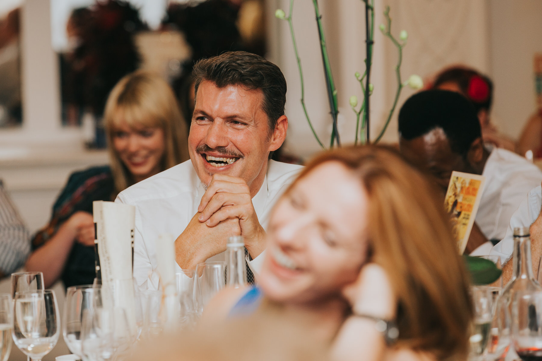 218 wedding guests laughing during speeches after meal.jpg