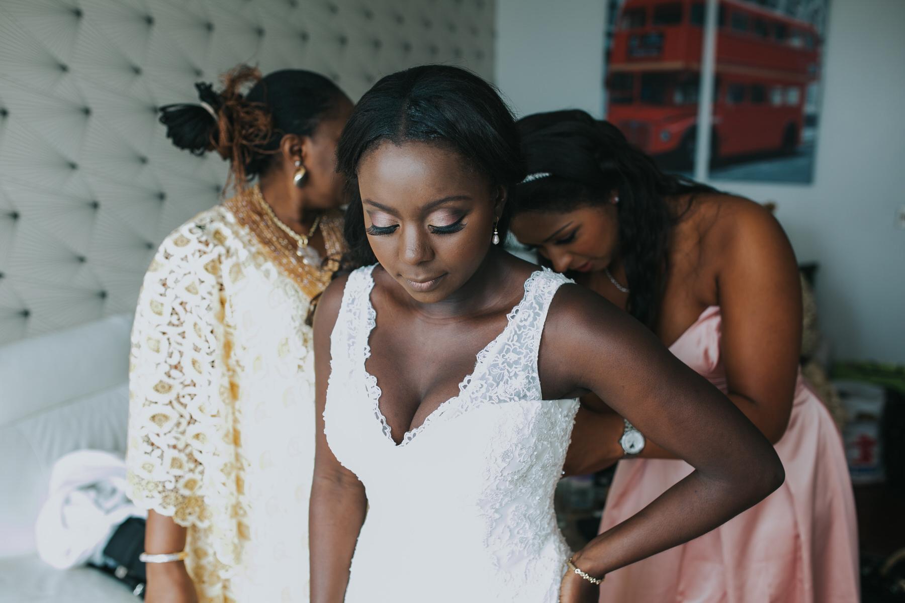 42-bridesmaid adjusting brides dress London wedding photos.jpg