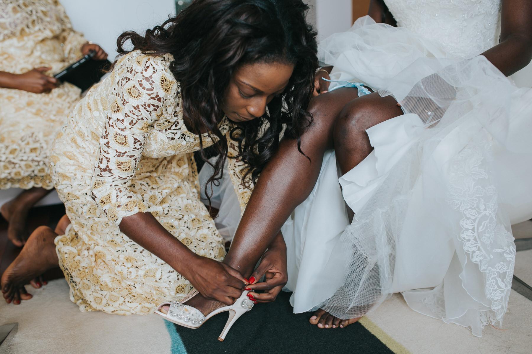 48- bridesmaid tying bride's Emmy London wedding sandal.jpg