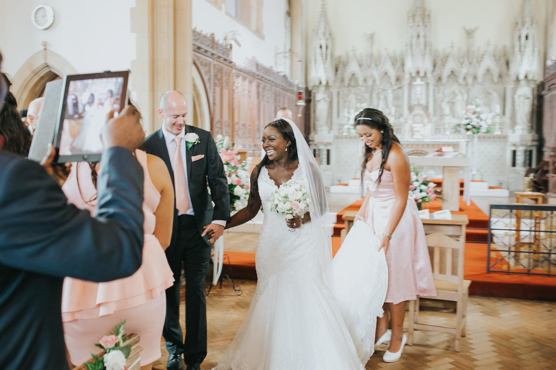 88 happy bride being papped by ipad bridesmaid straighten dress.jpg