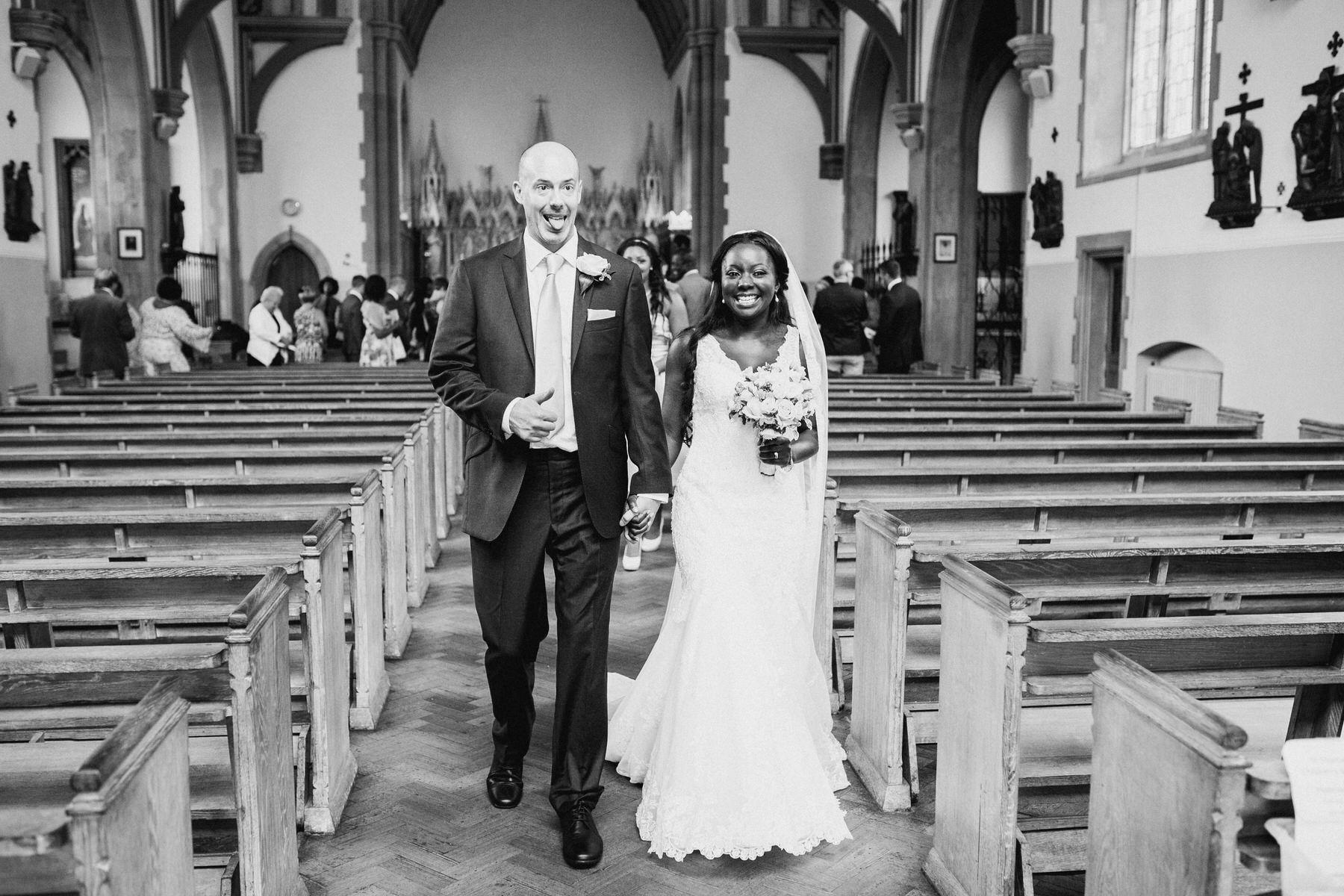 90 happy groom signalling walking out of church.jpg