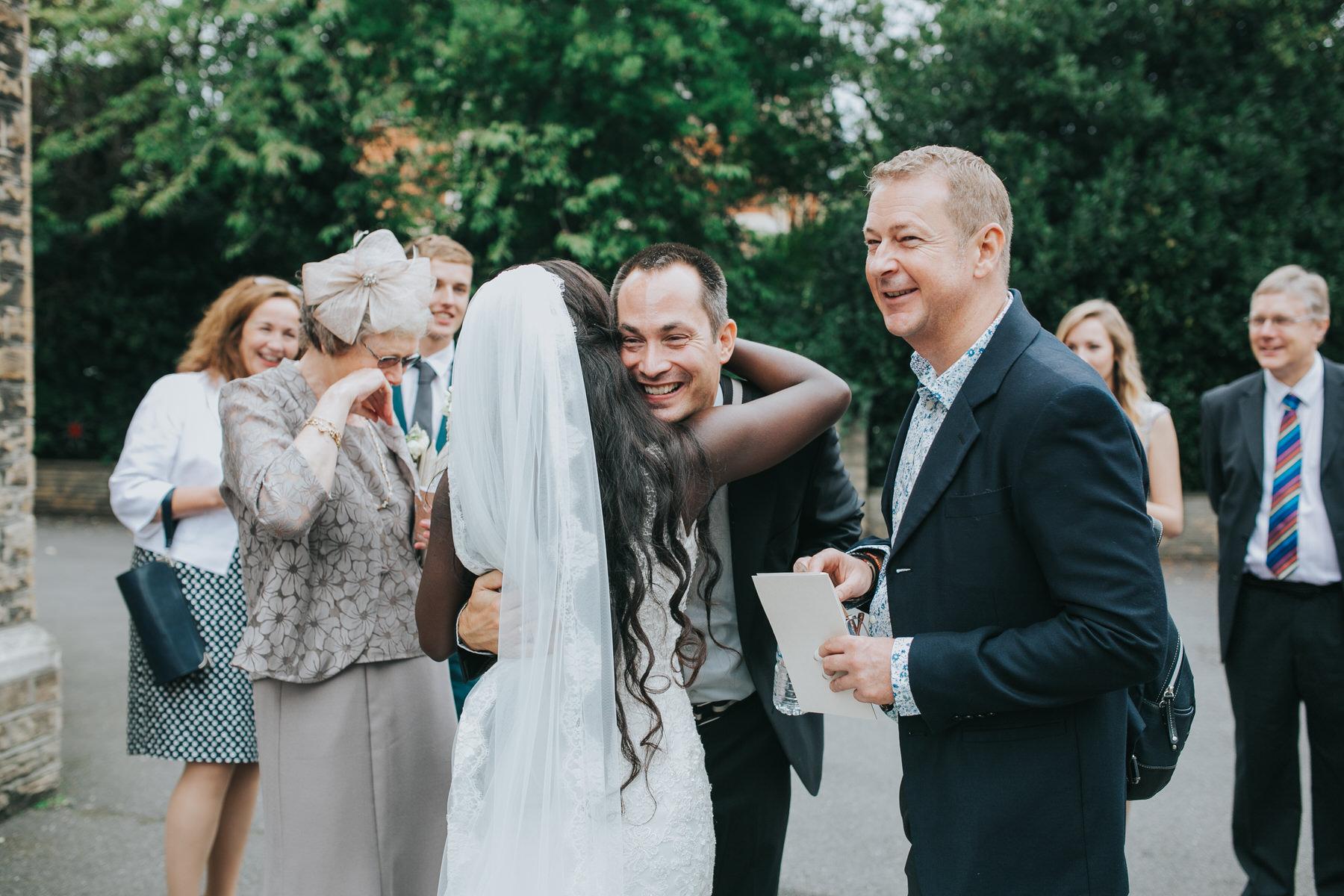 100 guests congratulating bride outside church.jpg
