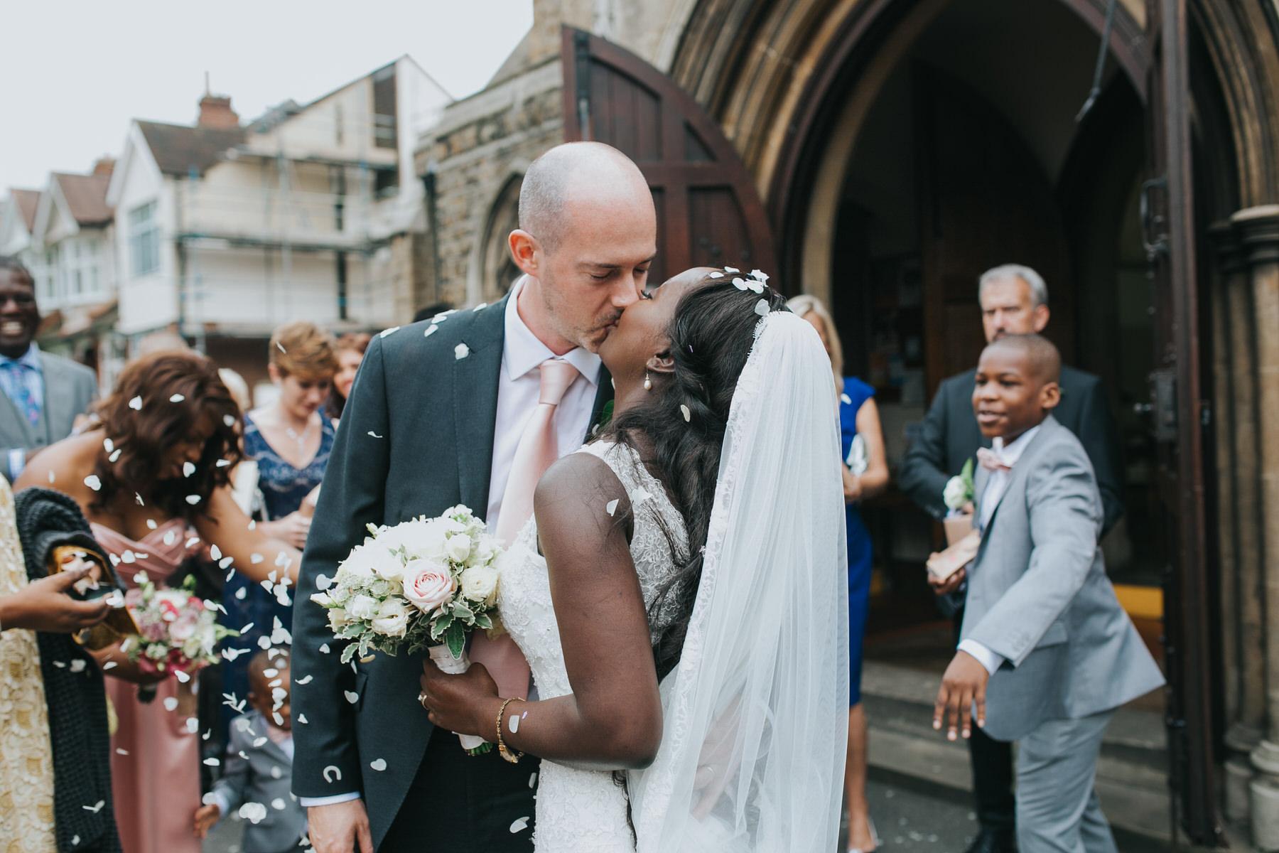 104 groom kissing bride during confetti outside church.jpg