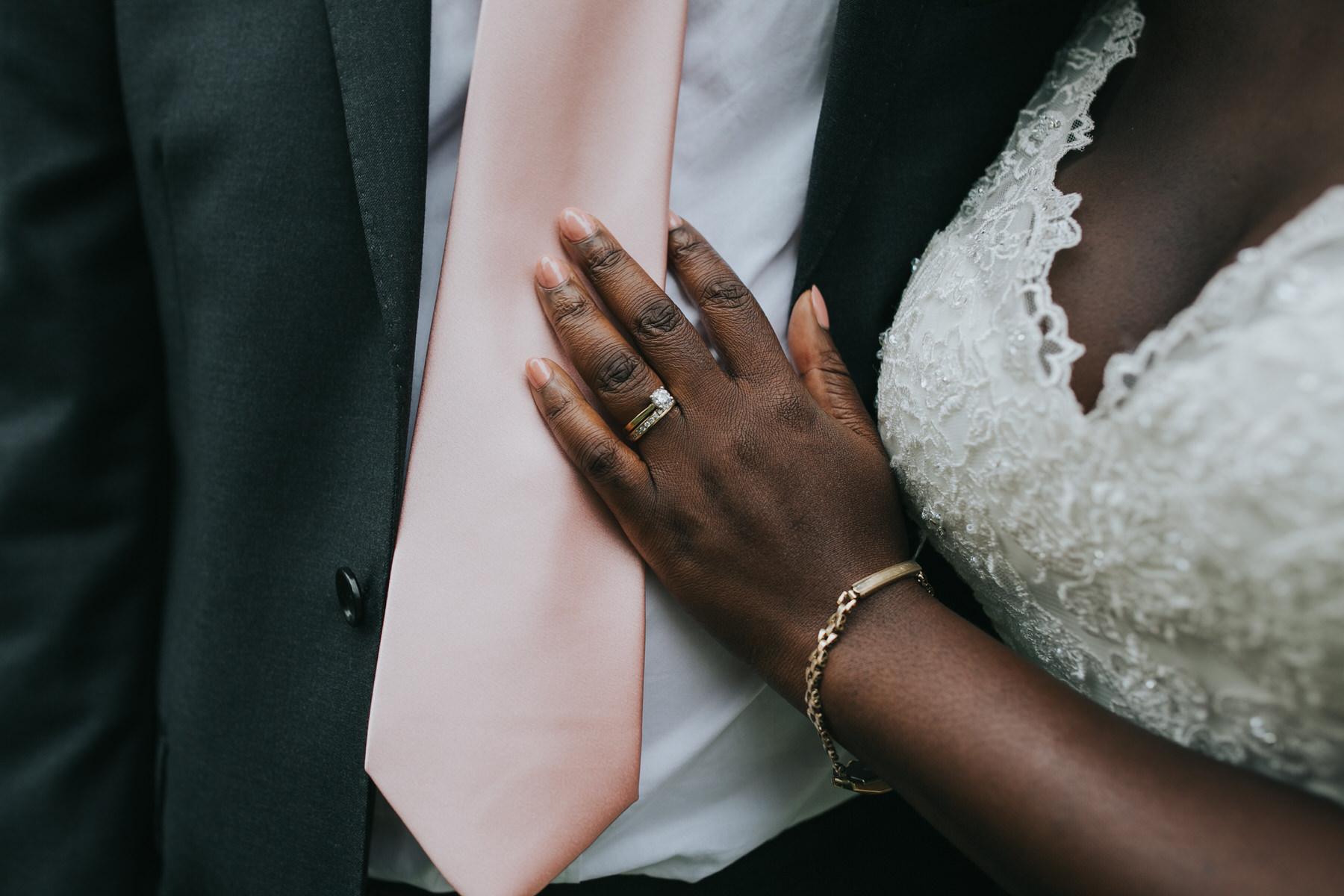 234 bride resting wedding ring hand grooms tie.jpg