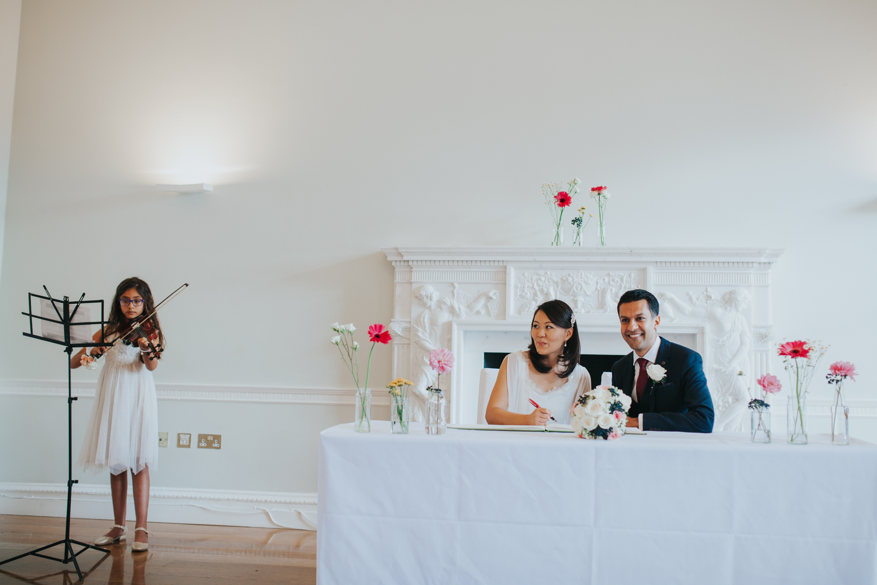 brides niece playing violin during signing of register Asia House London wedding photography