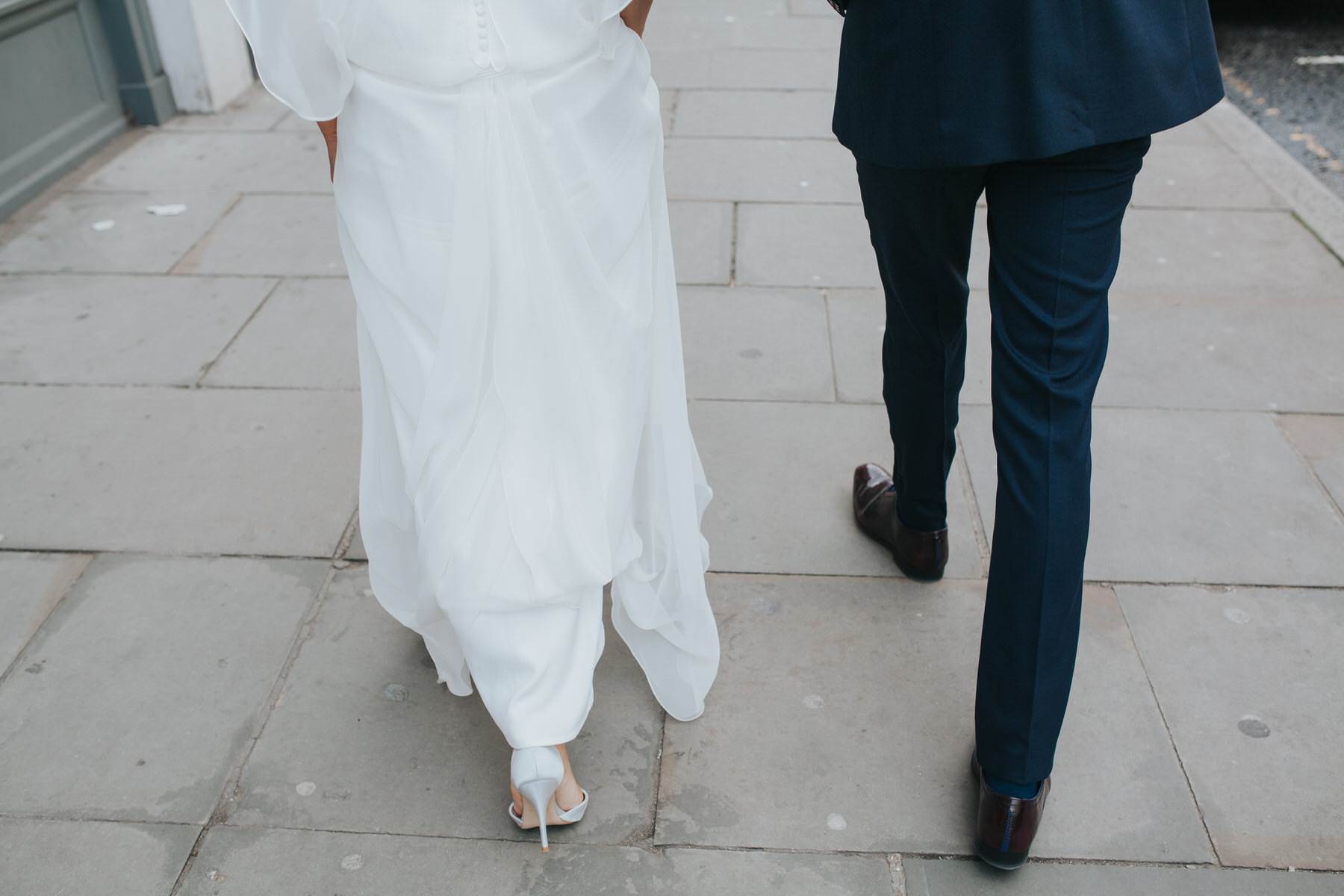 the hem of brides dress with sandals peeking