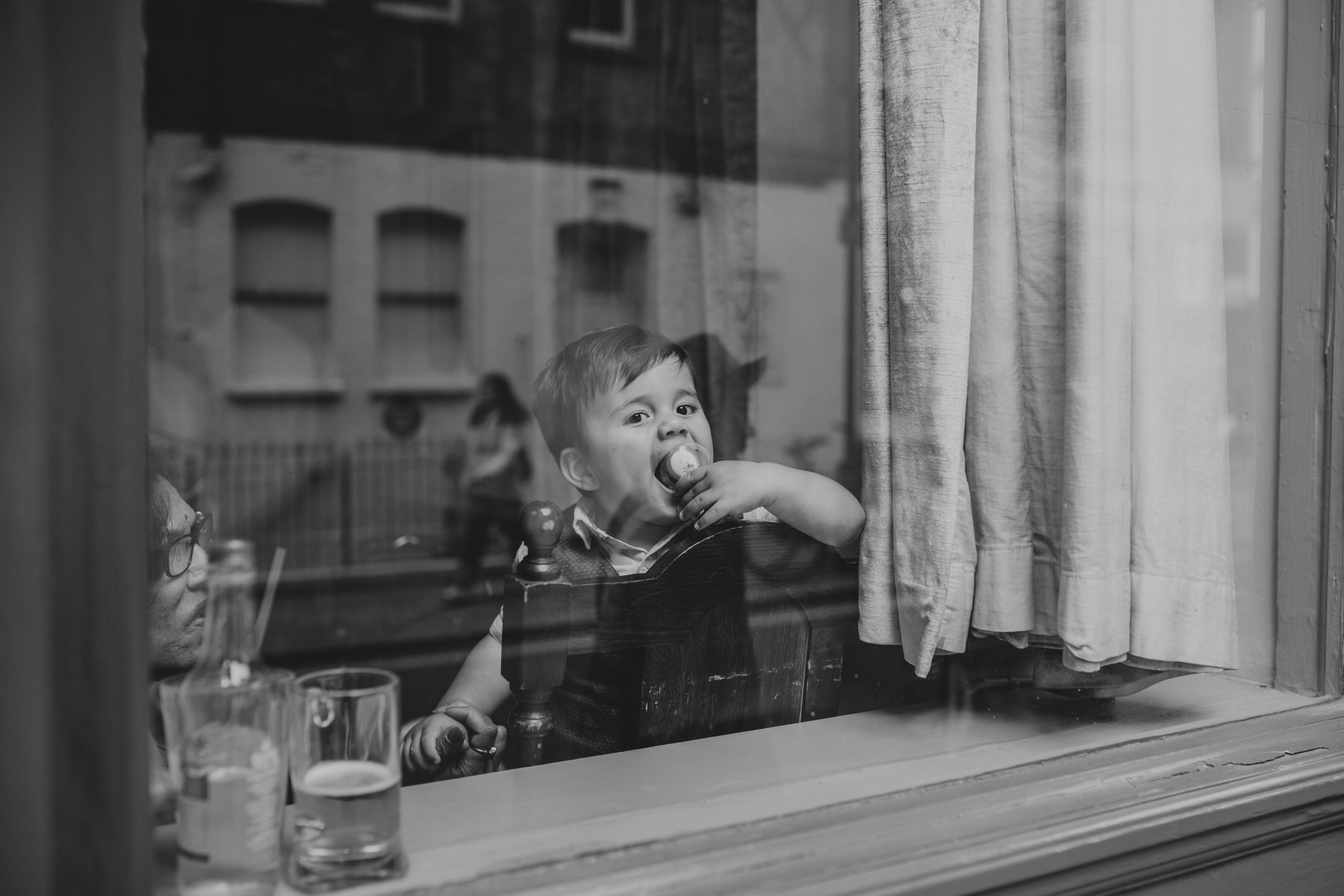 cute child wedding guest playing window London drinks reception