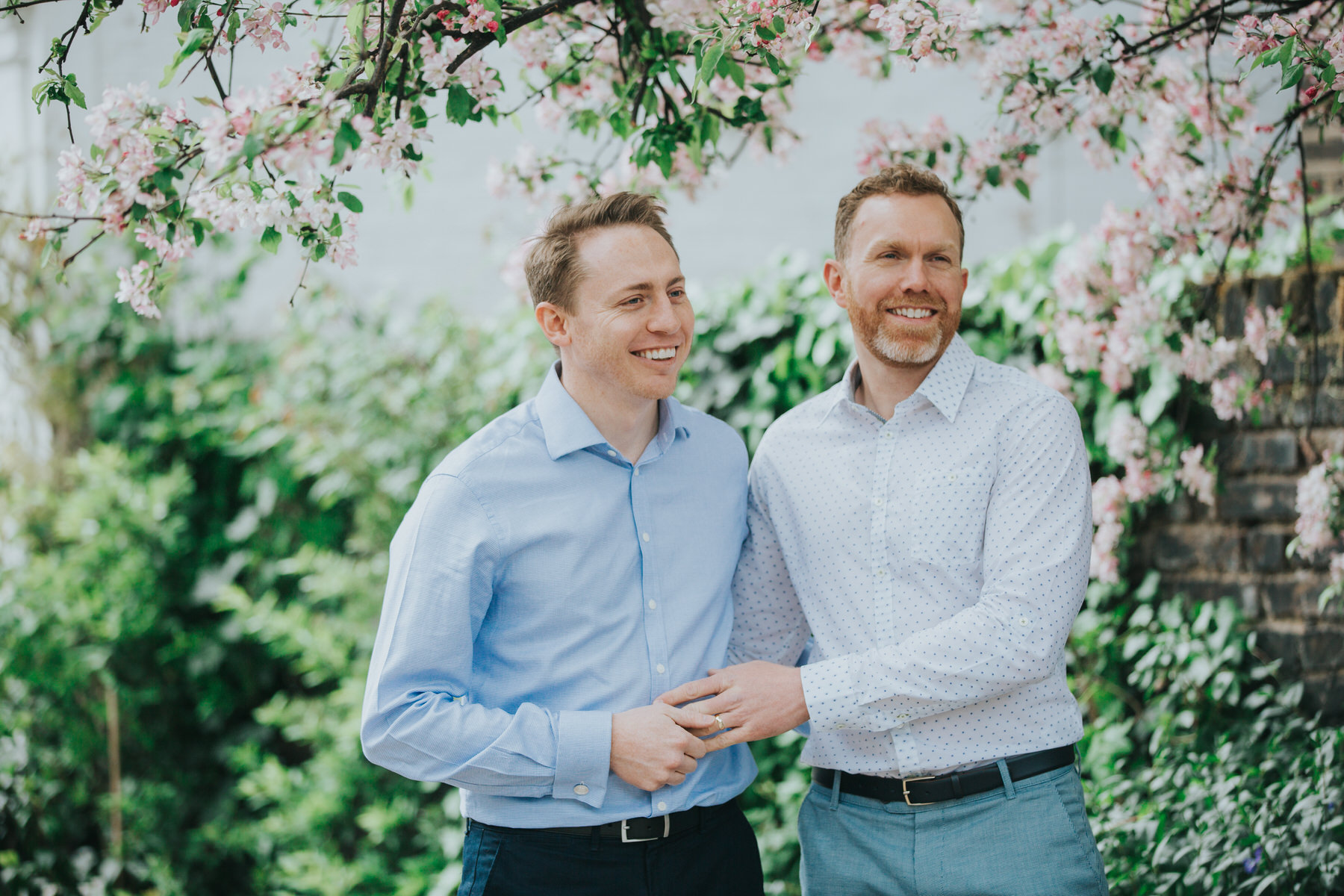 43 natural moment between two grooms Chelsea wedding cherry blossoms.jpg