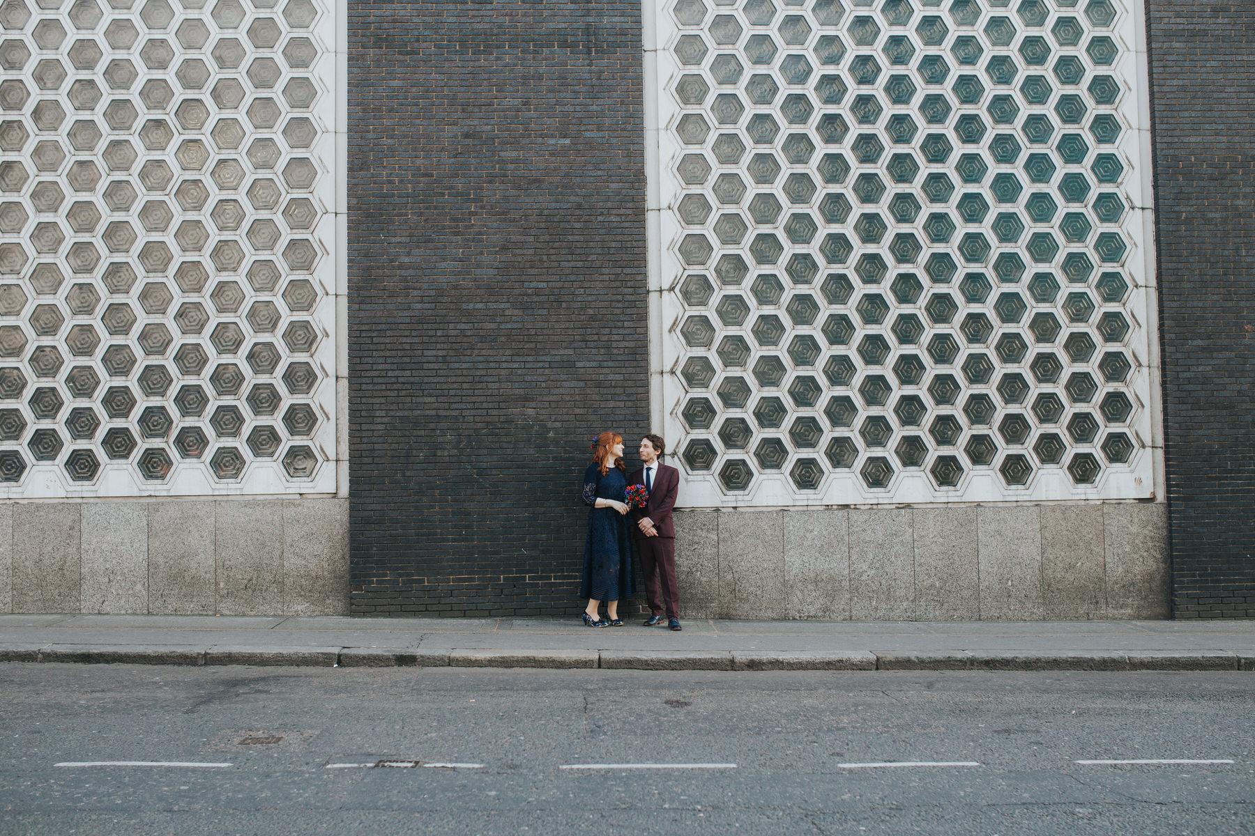 61 individualistic bride posing groom honeycomb wall London wedding photographer.jpg