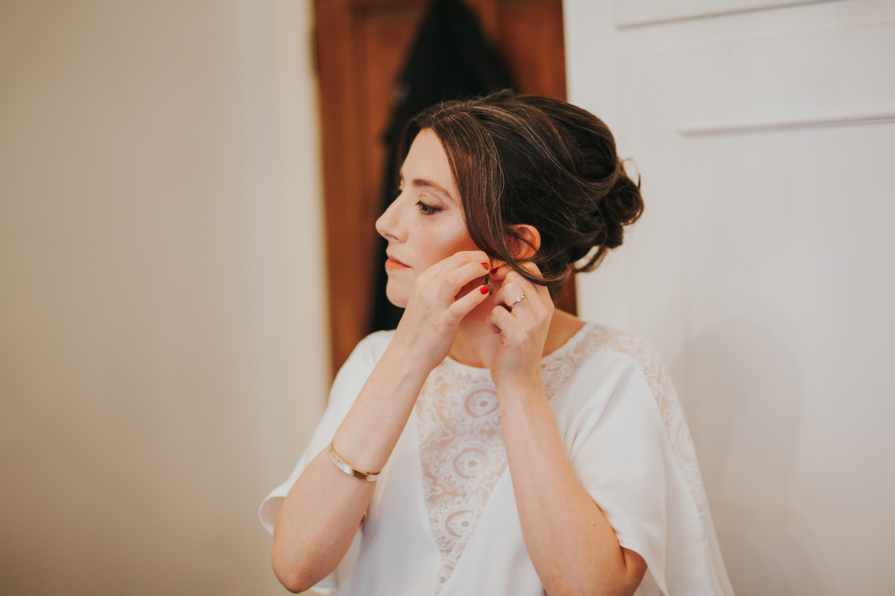 31-bride clipping earing getting ready Minna wedding dress.jpg