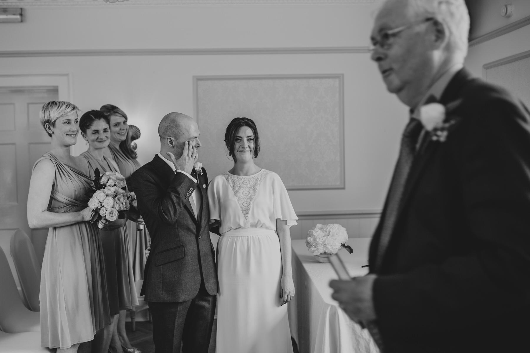 106 BW wedding reportage emotional groom brushing tear away.jpg