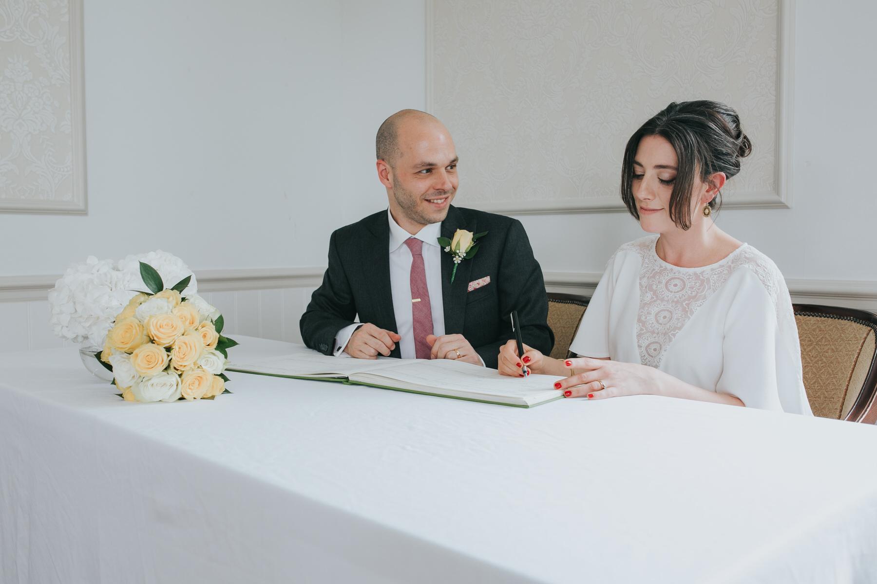112-Belair House bride signing register groom.jpg