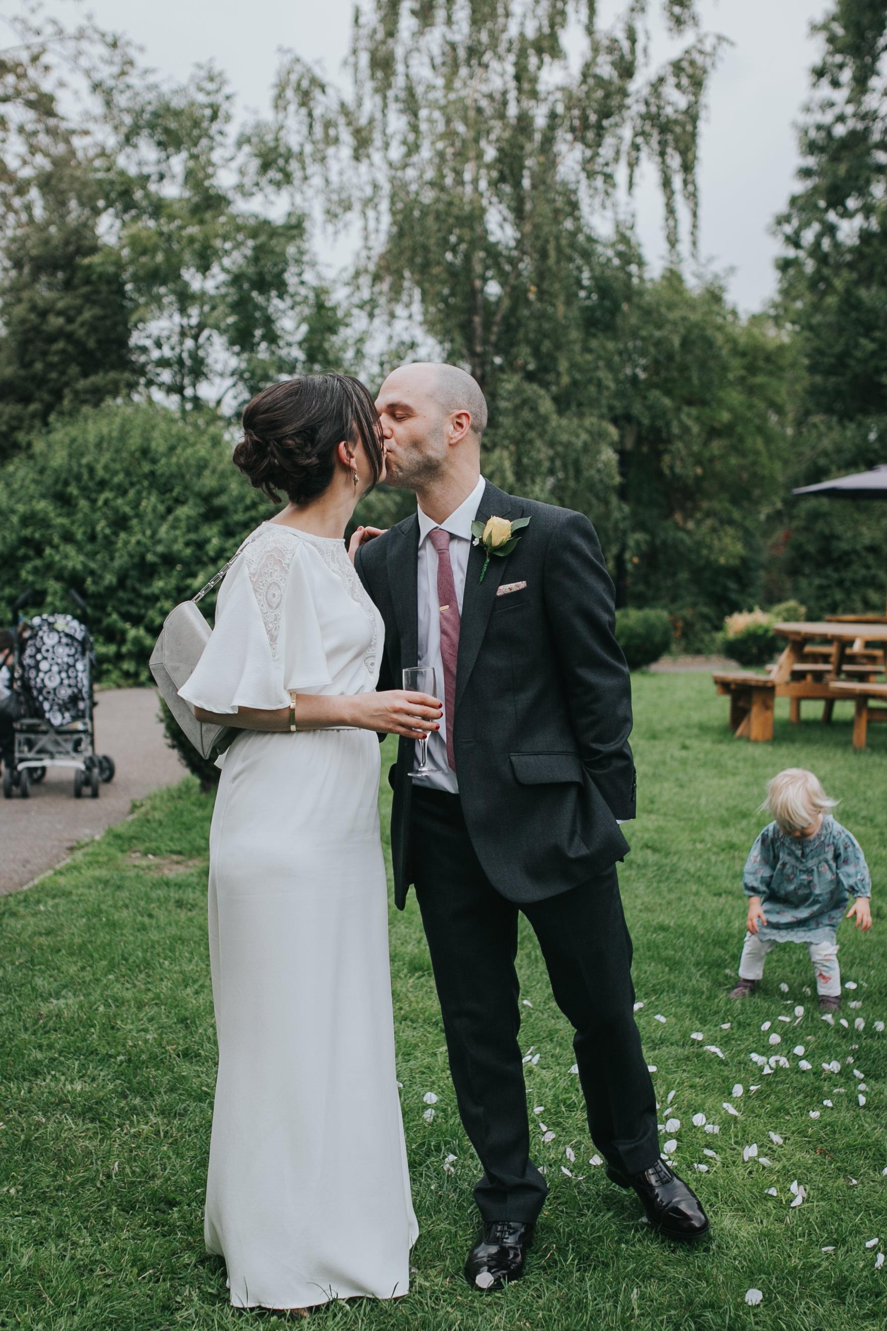 241 bride kissing groom Belair House lawn.jpg