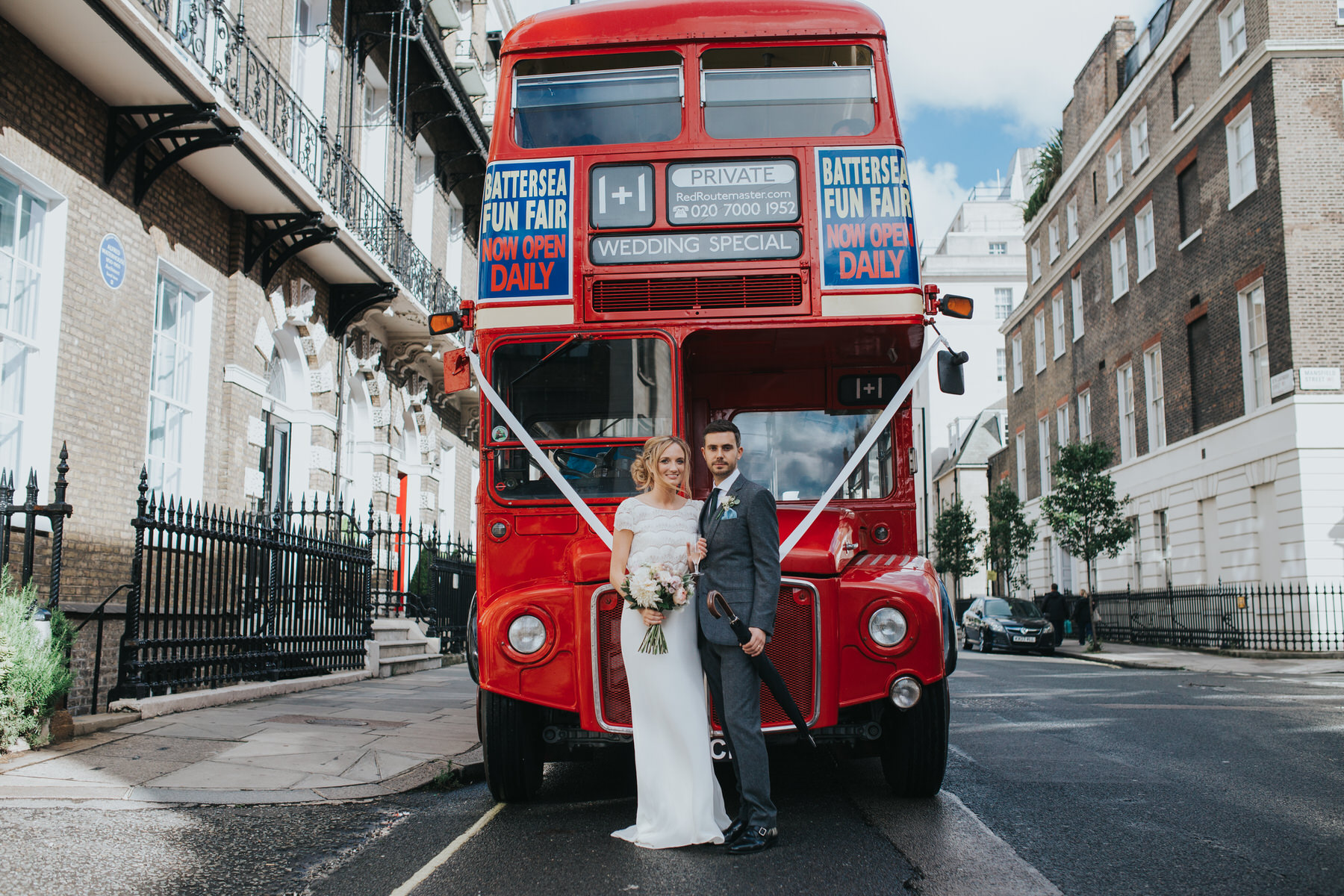 bride groom posing red wedding bus outside Asia House Marylebone.jpg