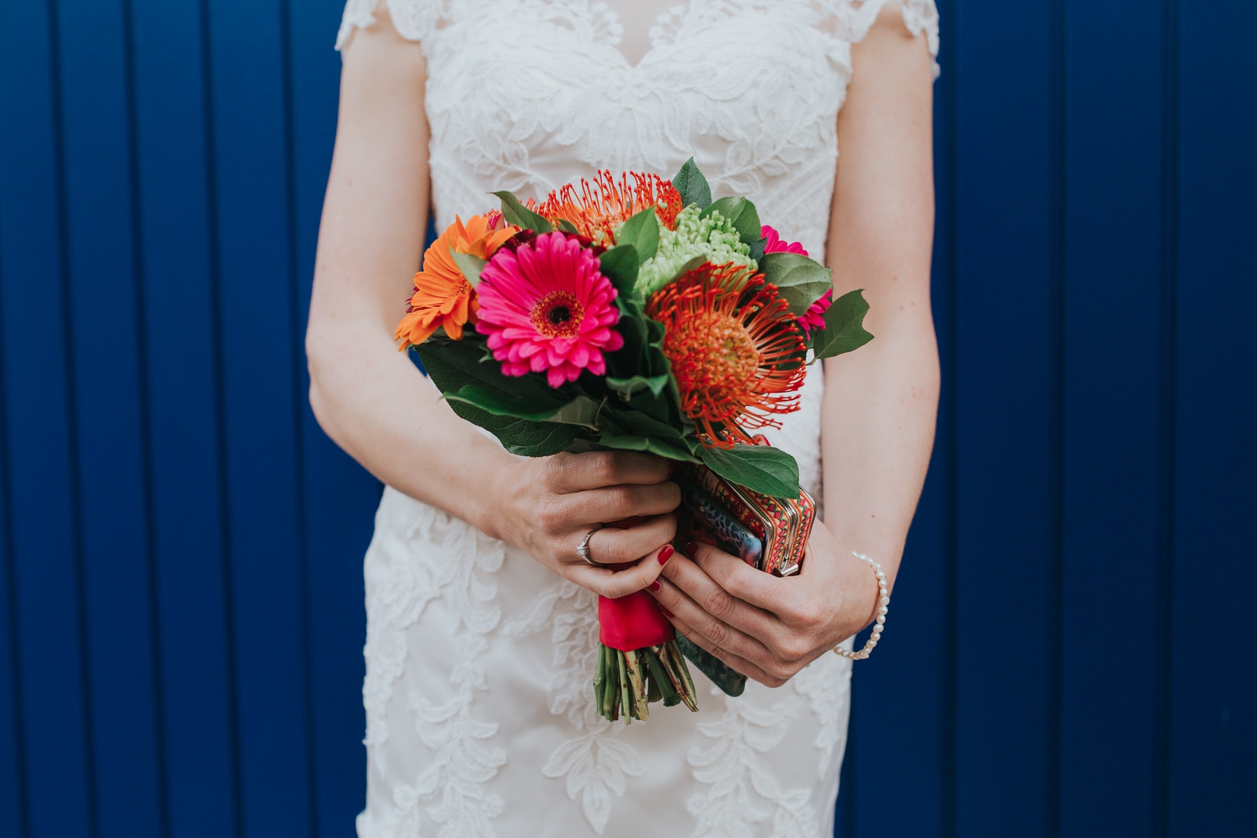 Bride holding bright ornage pink bouquet proteas barbetondaisy.jpg