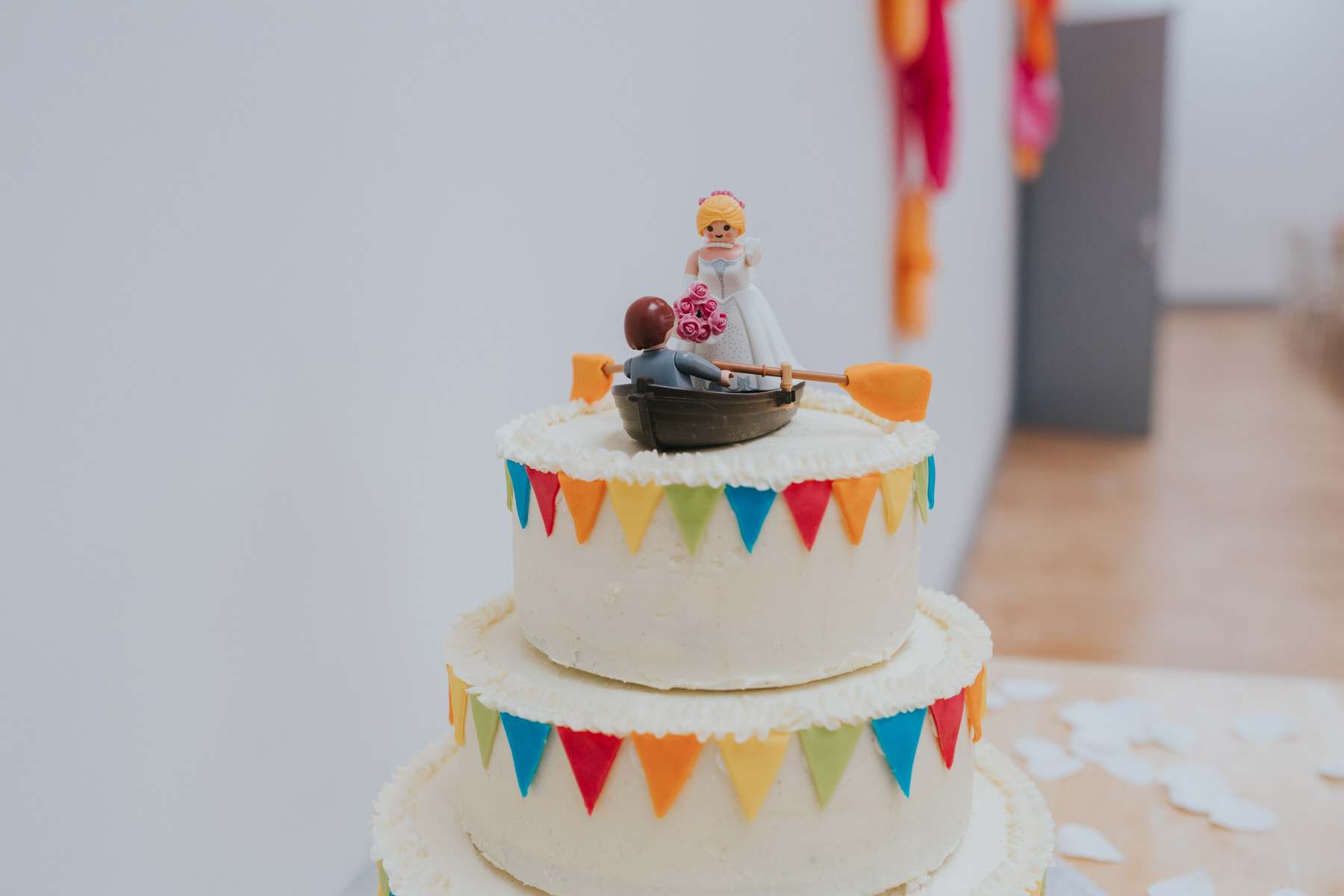 Rowing themed wedding cake with colourful flags lego bride groom figurines.jpg