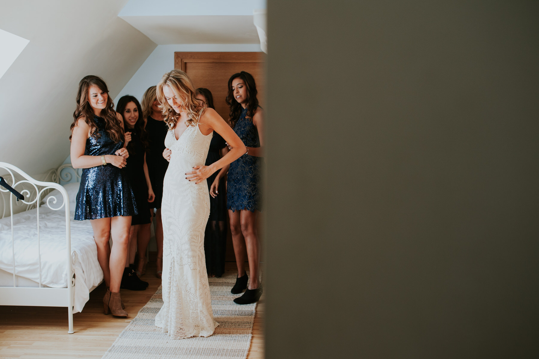 7 bride puts on cream crocheted wedding dress bridesmaids watching.jpg