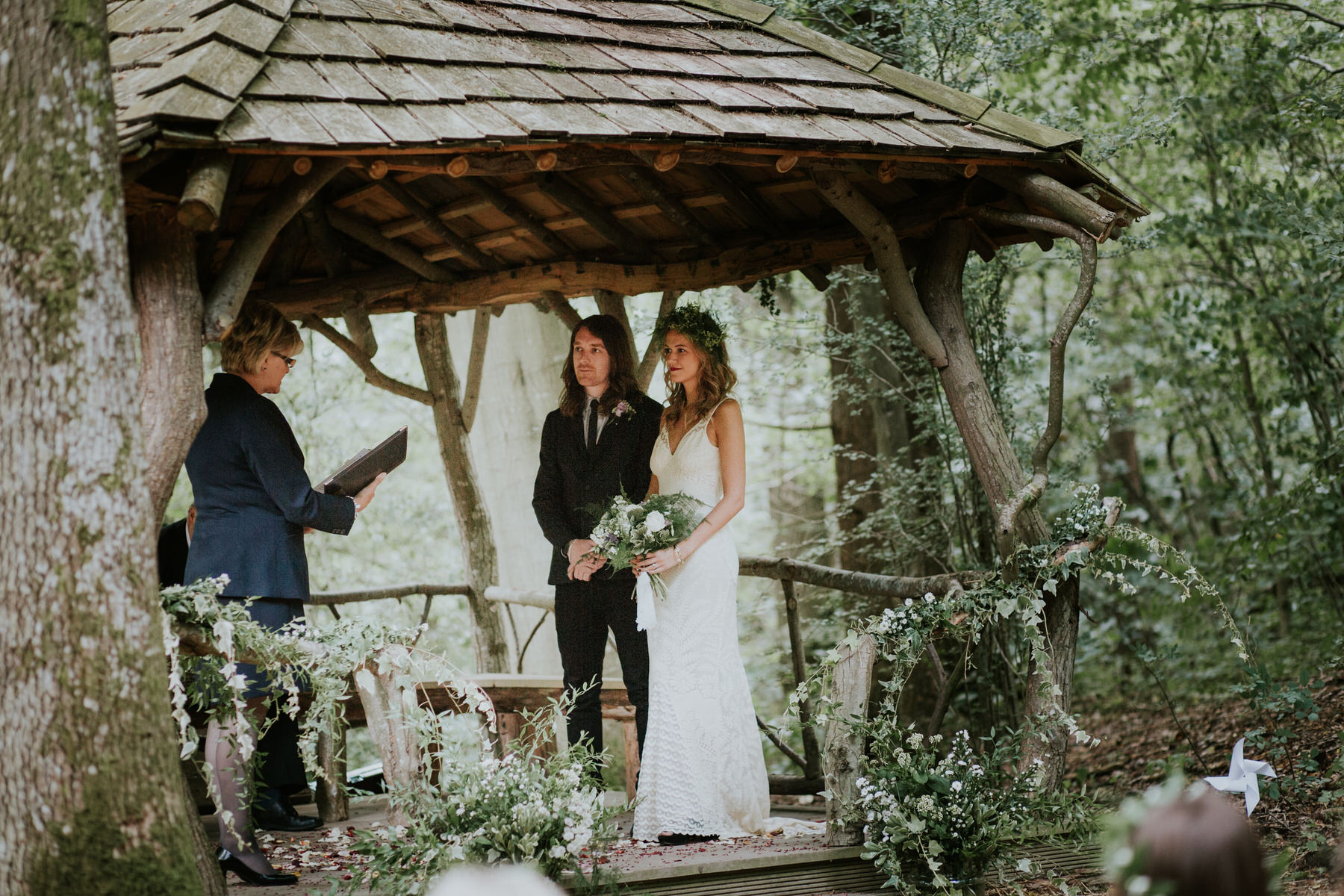 29 groom bride celebrant woodland outdoor wedding ceremony under wooden bower.jpg