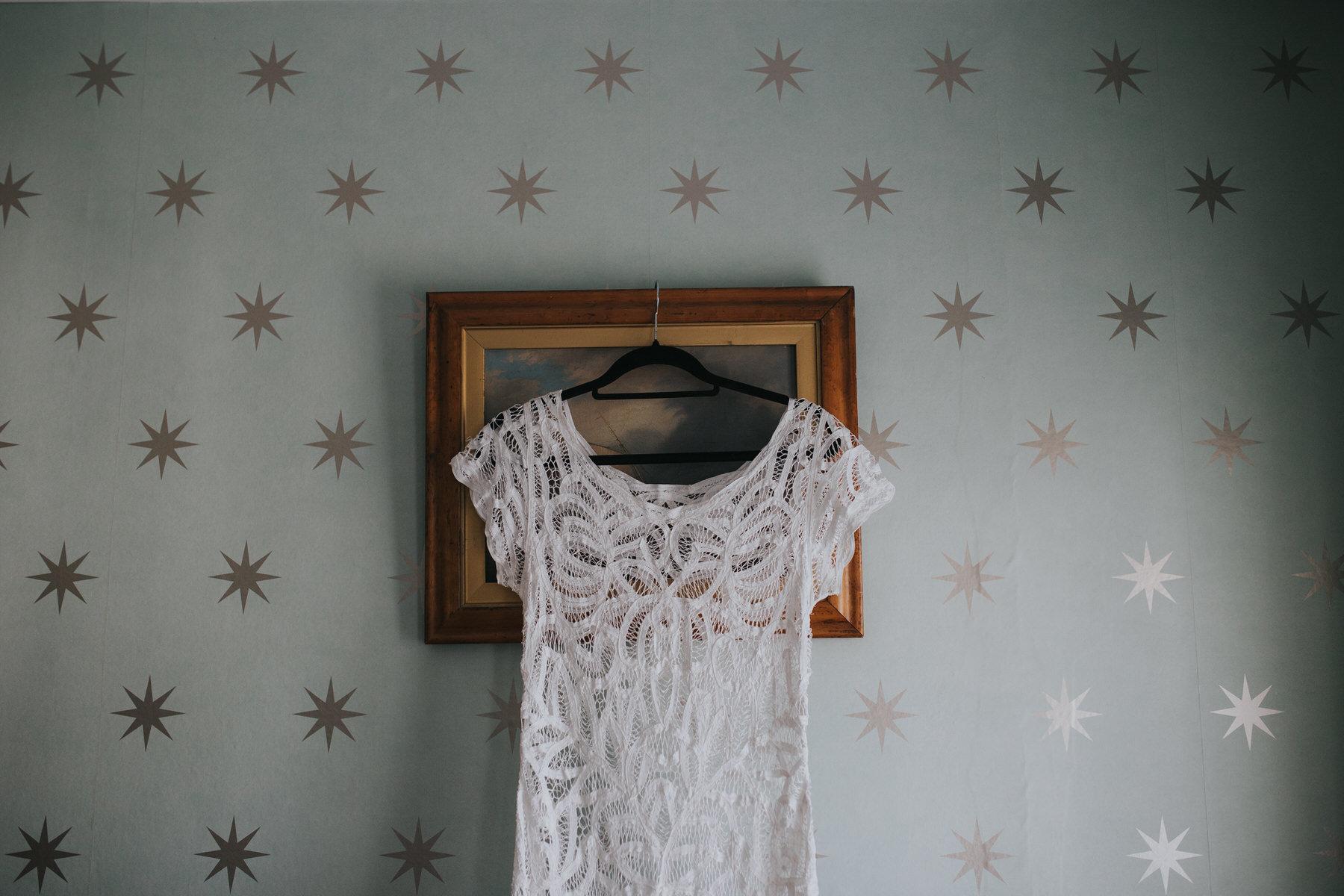 180 lace wedding dress hanging against silver star wallpaper Portmeirion.jpg