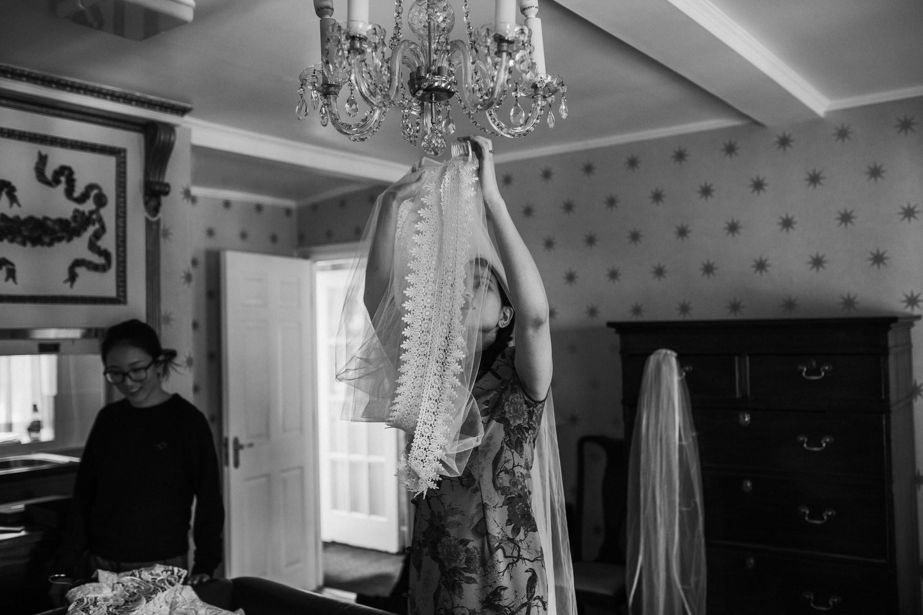 186 bride Shaina hanging  wedding veil chandelier Portmeirion documentary photographer.jpg