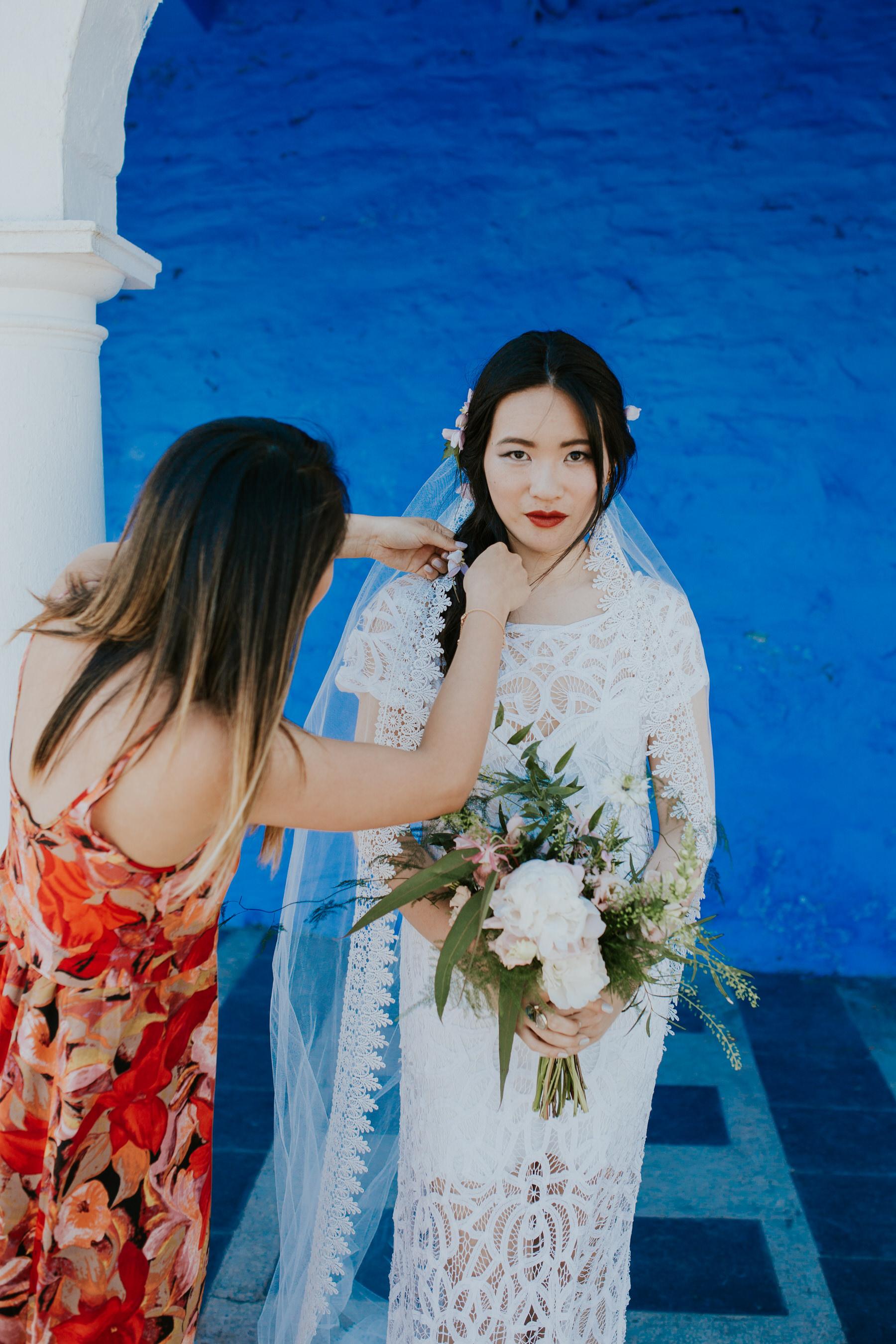 630 bride Shaina's having her veil tweaked by bridesmaid Portmeirion.jpg