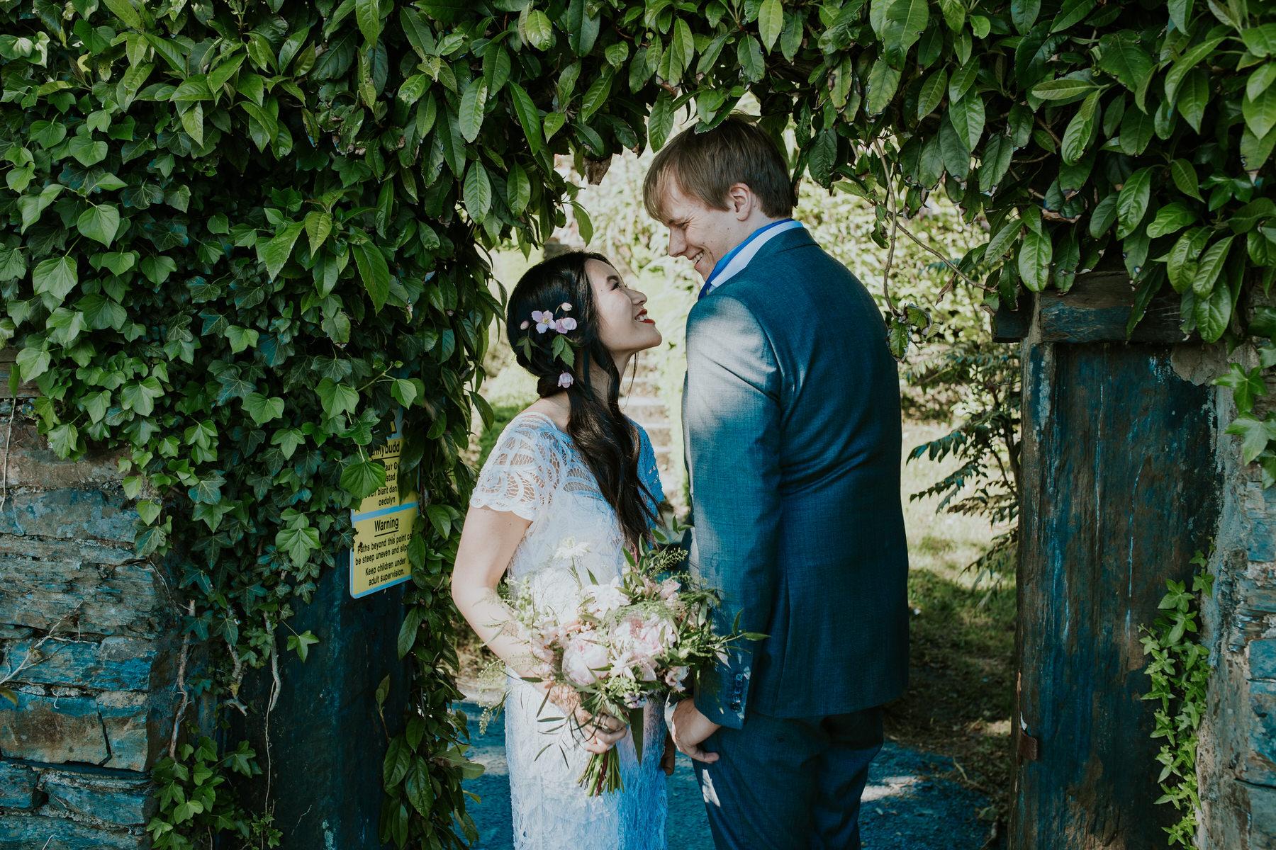 712 Portmeirion bride groom wedding portrait green arch.jpg