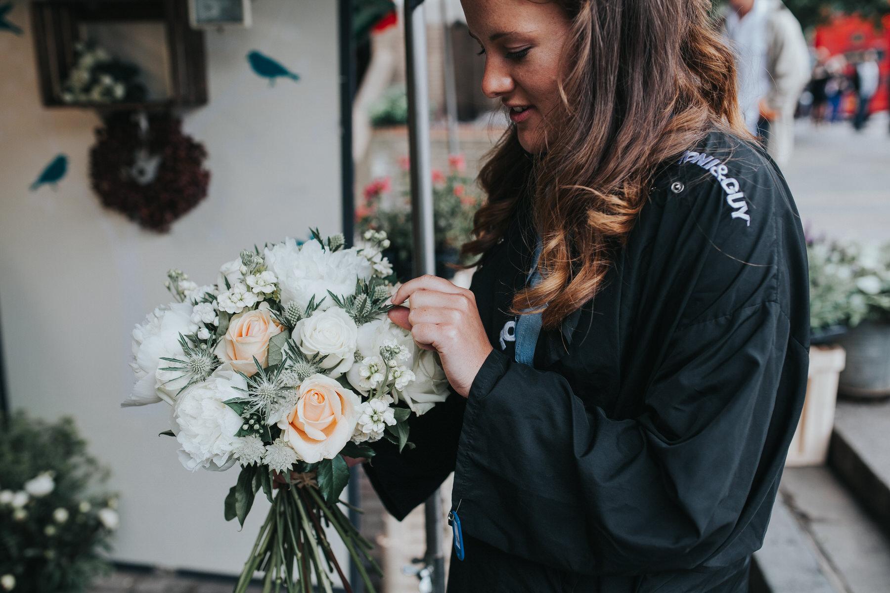 10 bridesmaid picking up brides bouquets.jpg