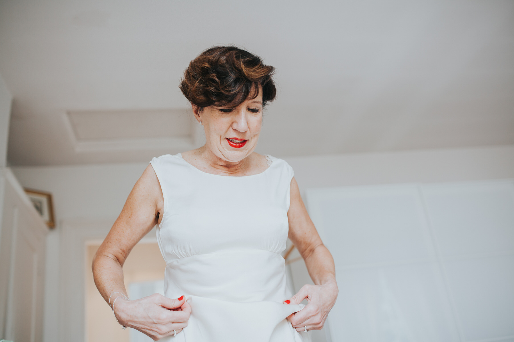 30 bride putting on Ghost wedding dress London.jpg
