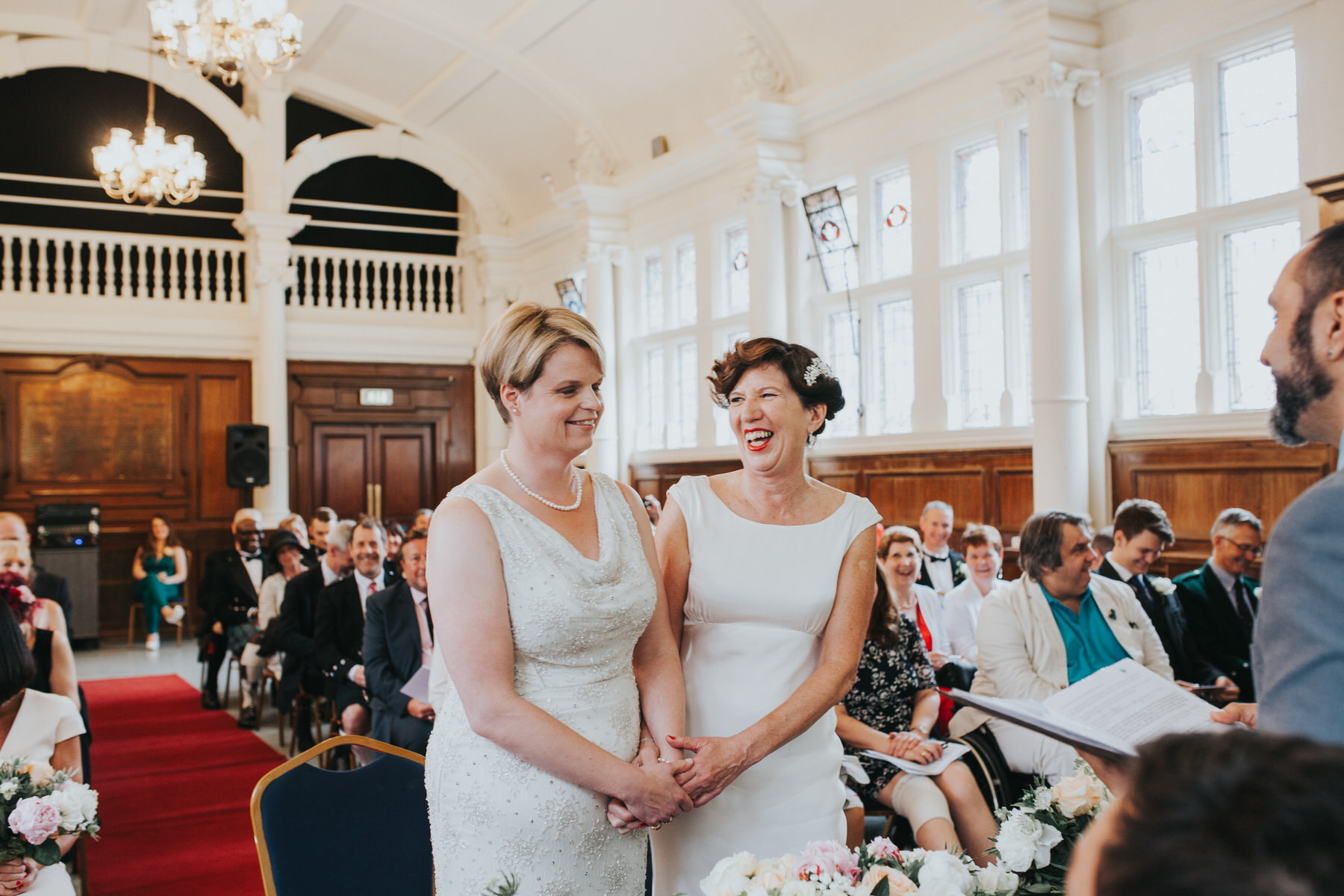 100 Old Finsbury Town Hall wedding ceremony two brides laughing.jpg