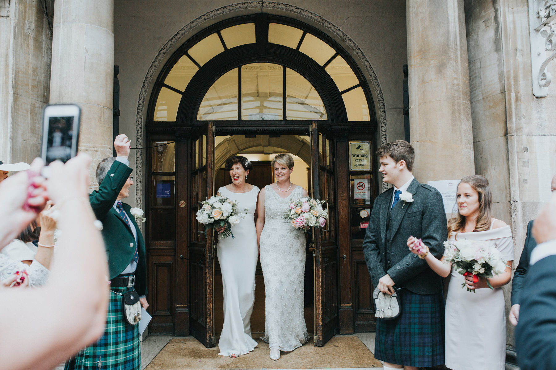 128 two brides exit Finsbury Town Hall wedding.jpg