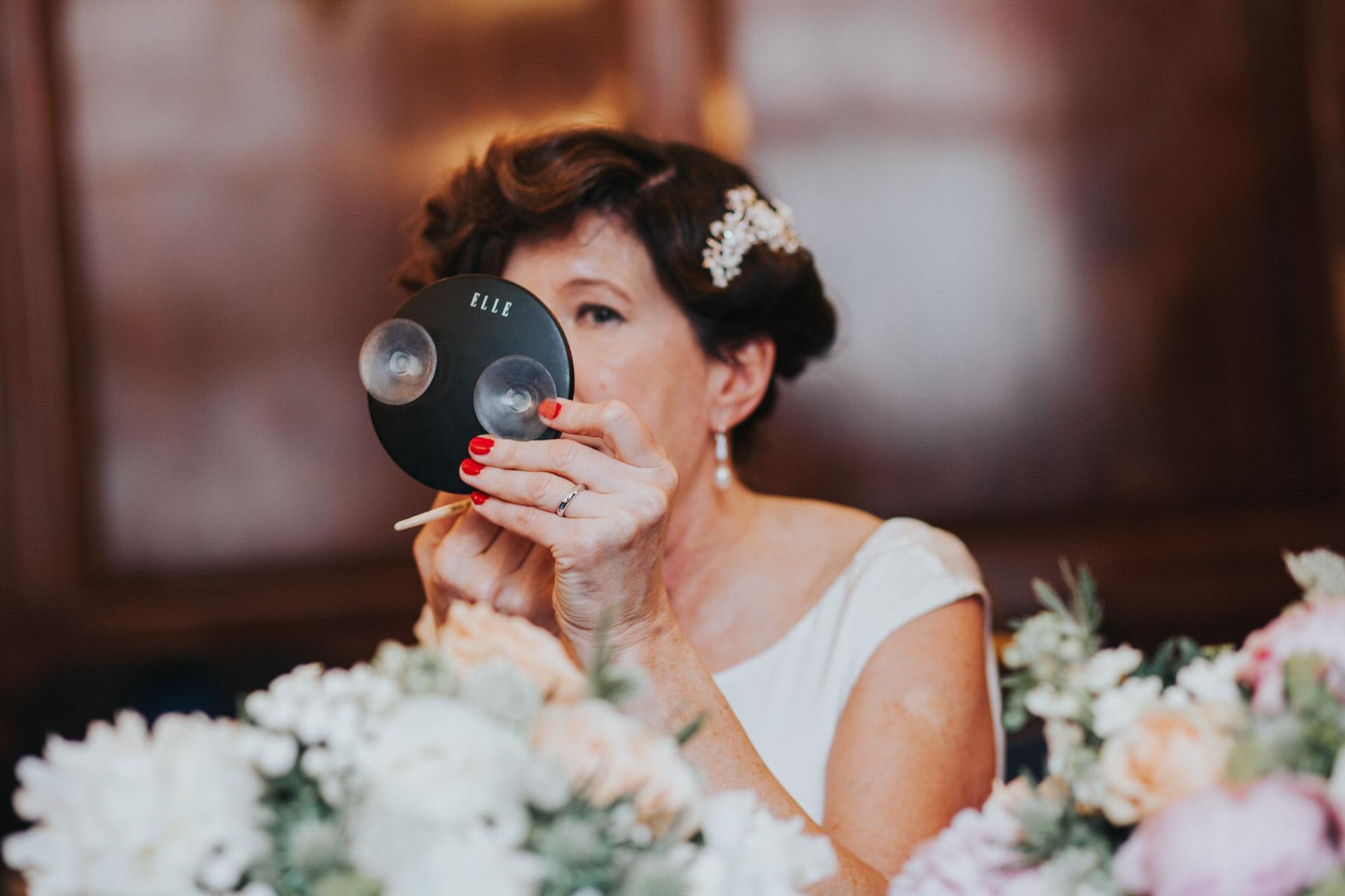 127 elegant bride touching up lipstick .jpg