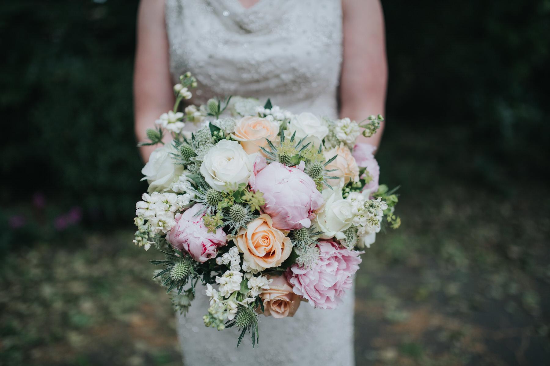 171 bride hoding bouquet thistle blush peony white rose.jpg