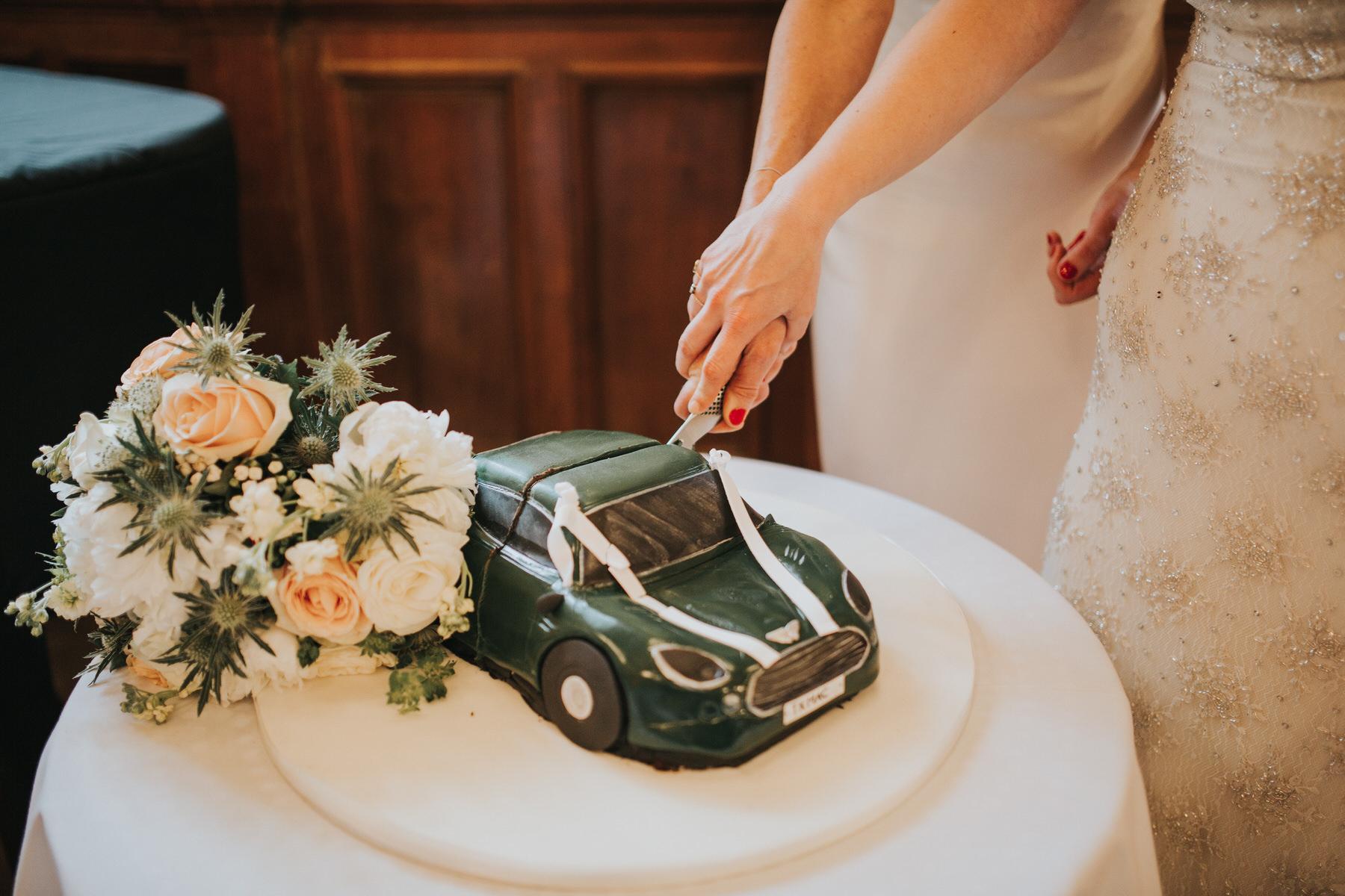 248 two brides cutting green sports car cake.jpg