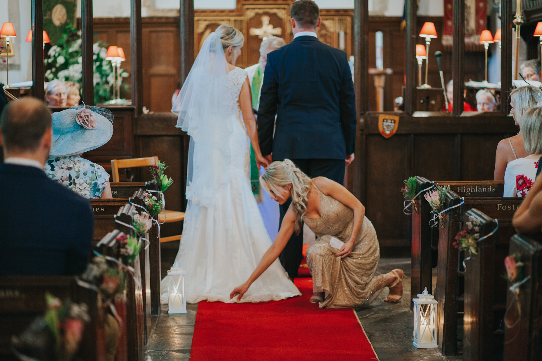 95 bridesmaid fixing brides train church wedding.jpg