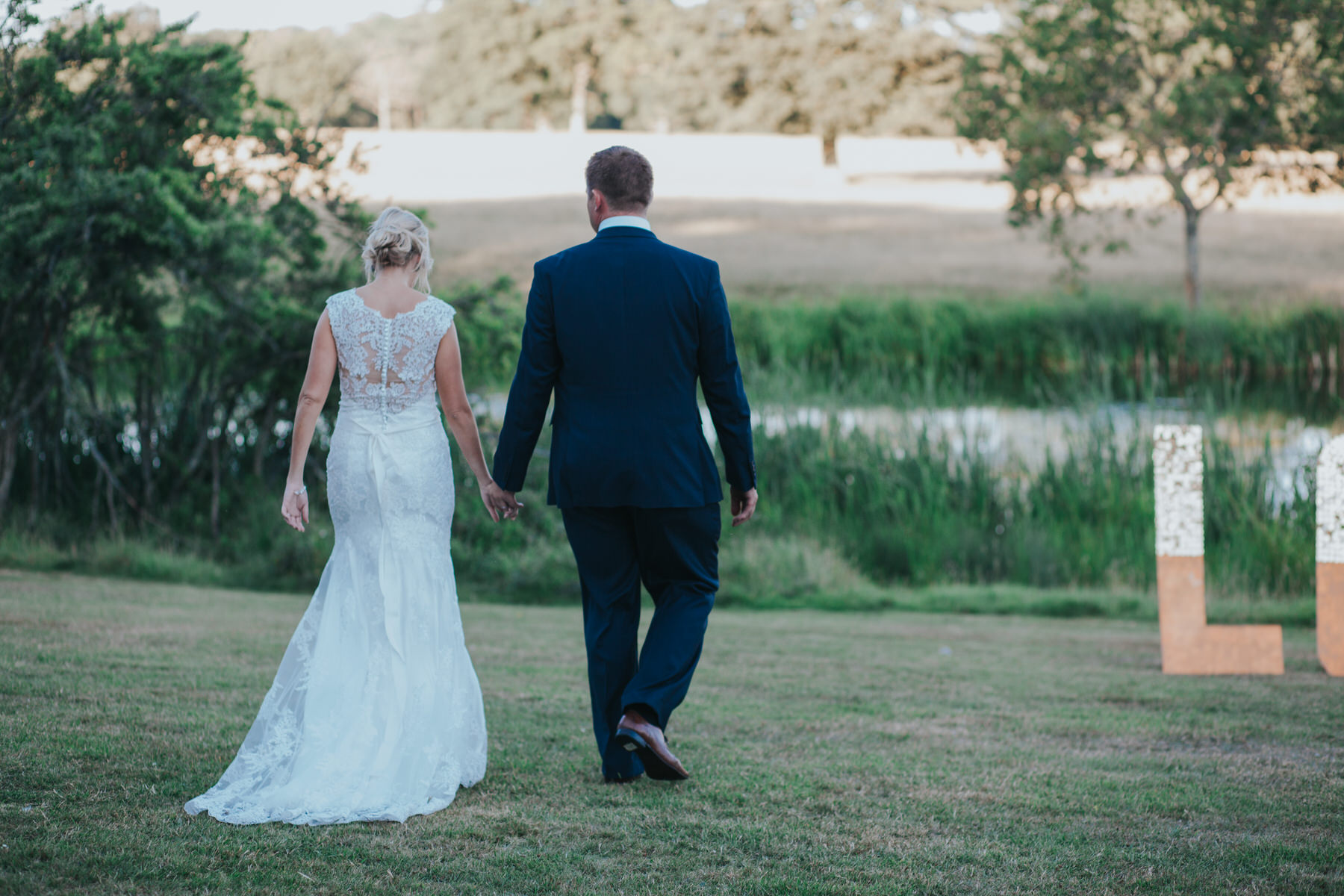 248 Knepp Castle newly married couple walk to pond.jpg