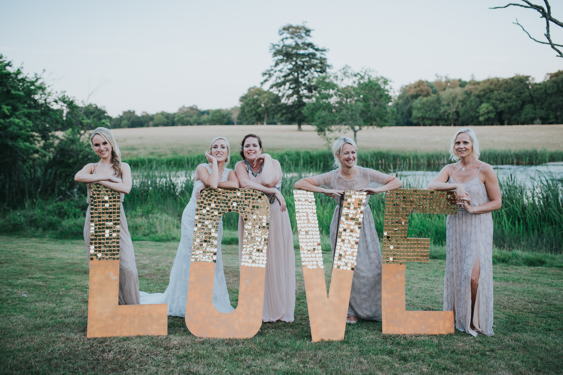 335 golden hour bride bridesmaid portraits Knepp Castle pond.jpg
