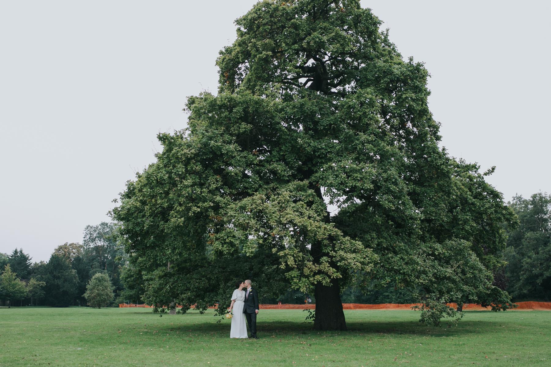 169 bride groom kissing under massive tree Belair Park London wedding.jpg