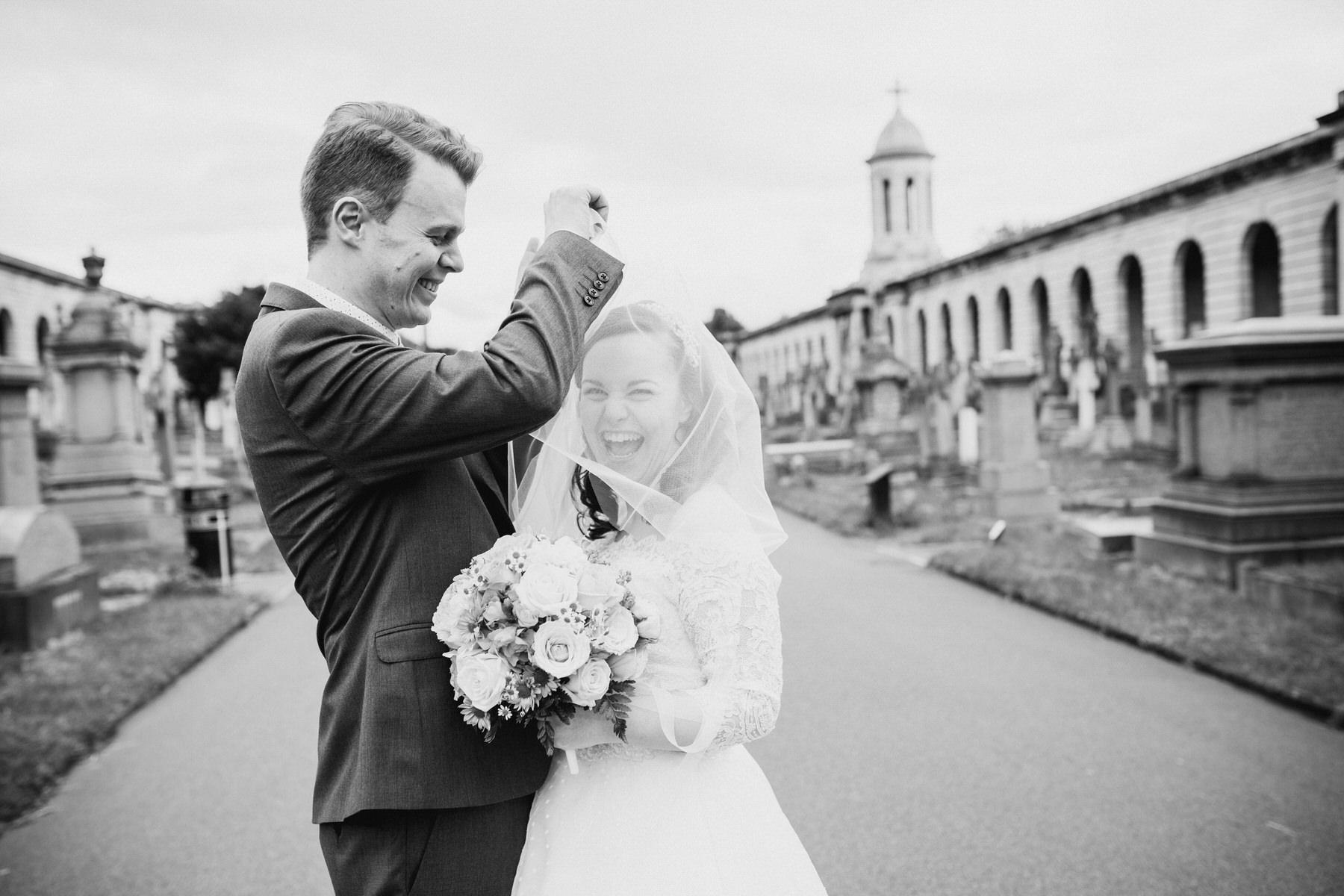 black and white groom unwraps bride windy veil.jpg