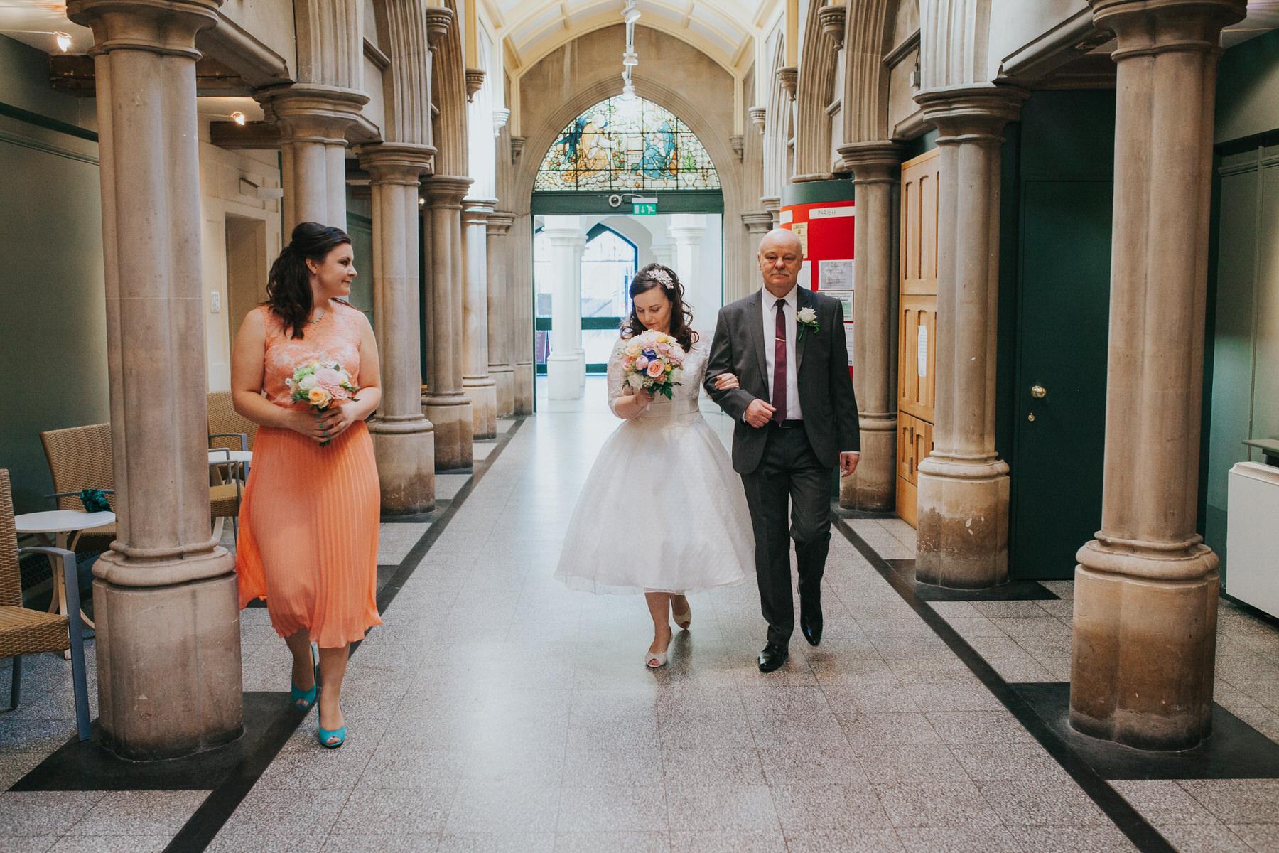bridesmaid peach dress walking bride arrive Fulham Catholic Church wedding.jpg