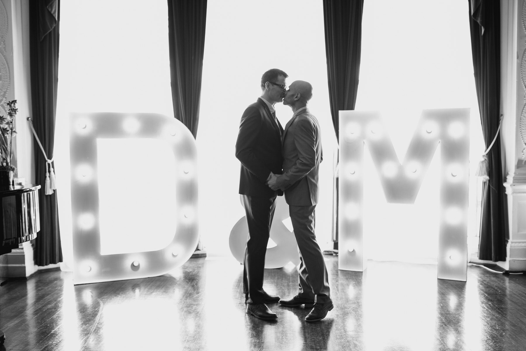 first kiss grooms equal marriage ceremony lit up letters.jpg