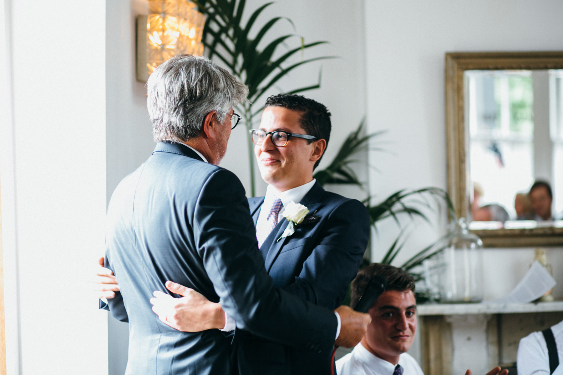 groom hugs father The Stag Hampstead wedding reception French English styling speeches.jpg