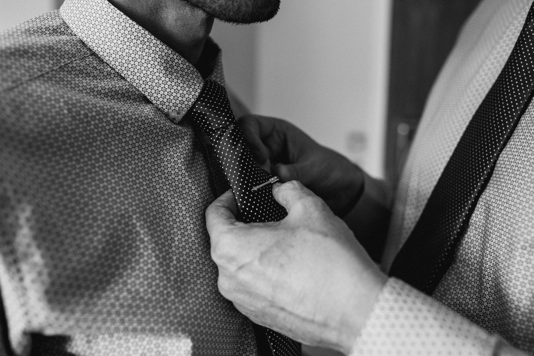 intimate photo of groom pinning tie clip.jpg