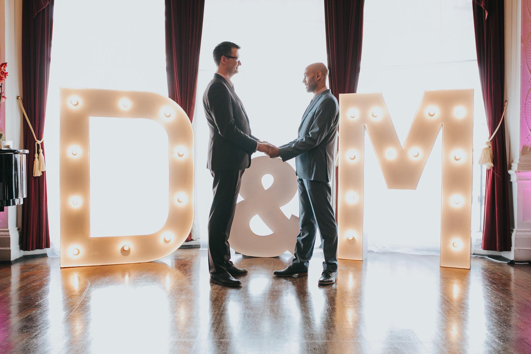 Same sex couple holding hands ceremony against large letters backdrop.jpg