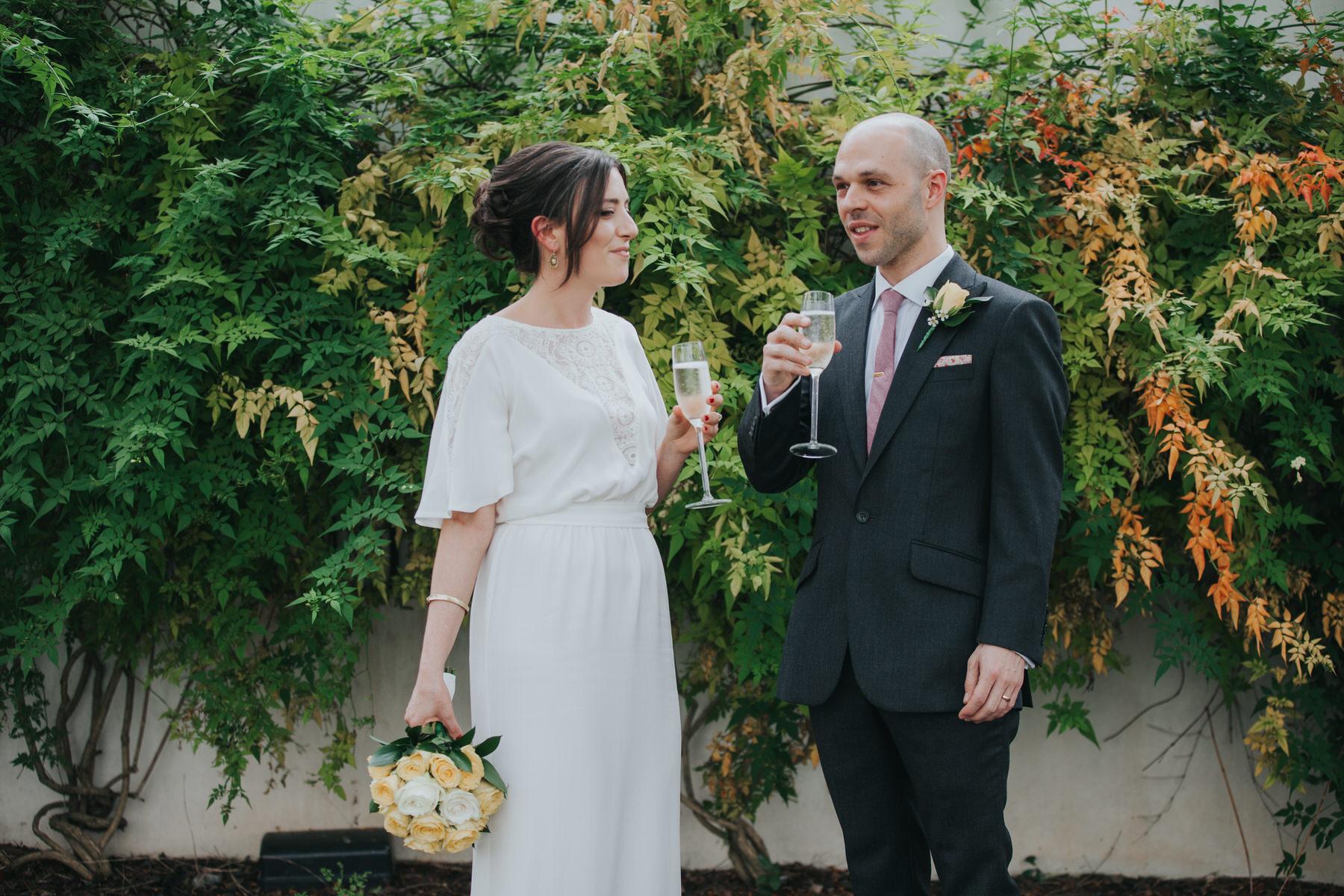 sneaky glass bubbly bride groom wedding reportage fern ivy wall.jpg