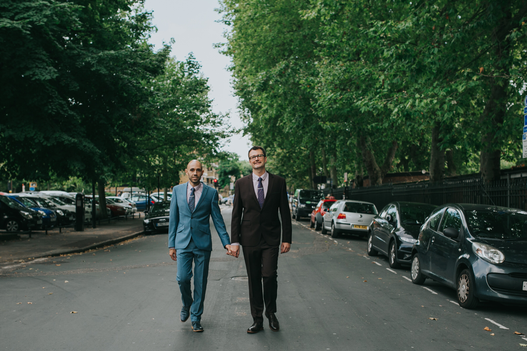 two grooms walking holding hands London road wedding ceremony.jpg