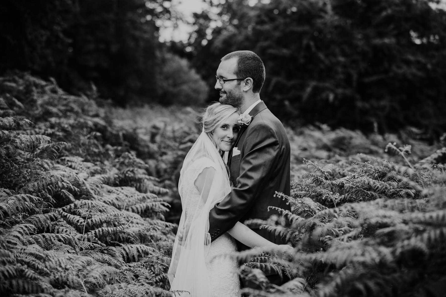 239 bride embrace groom couple portraits Pembroke Lodge ferns.jpg