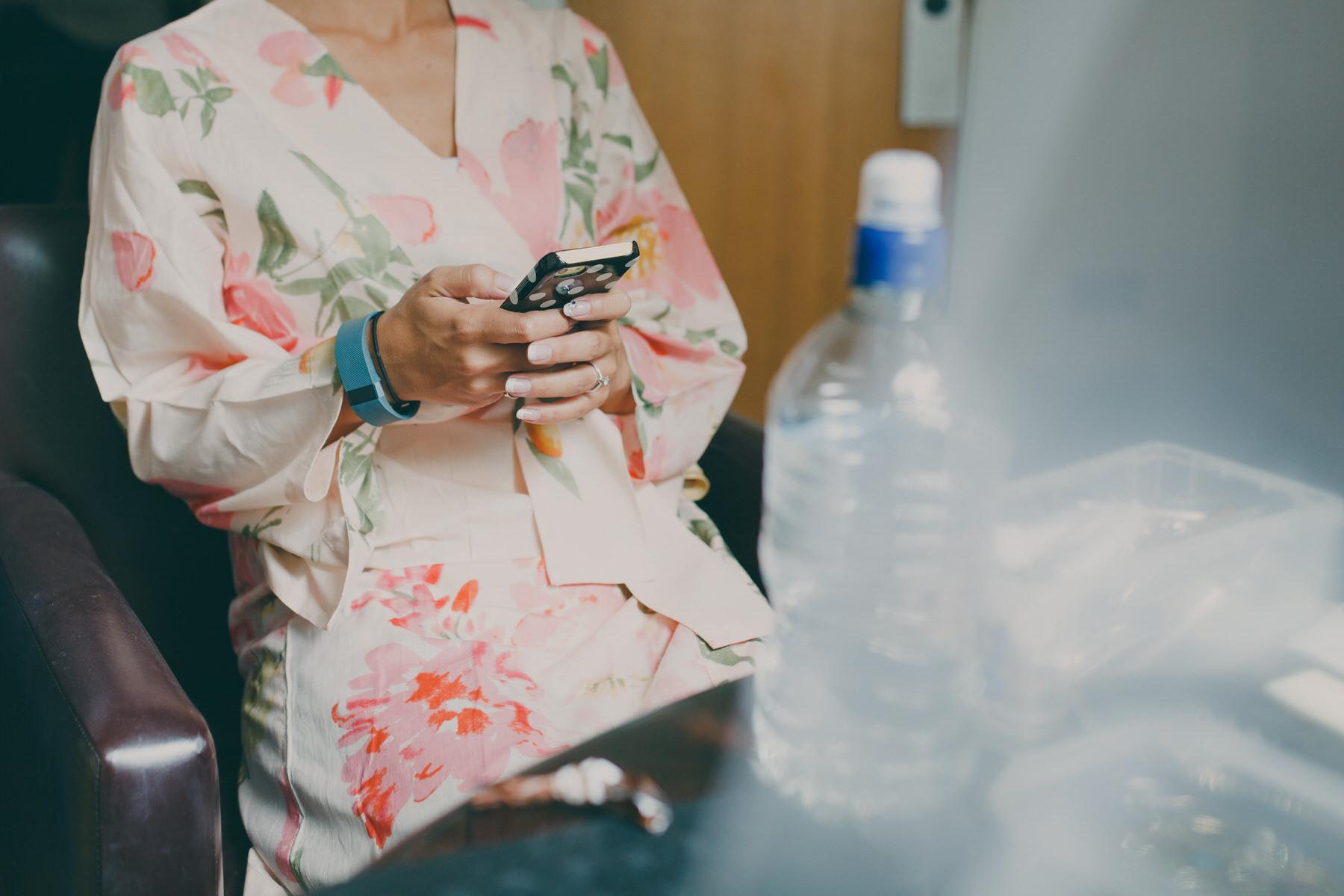 21 bride checking mobile pink kimono gown.jpg