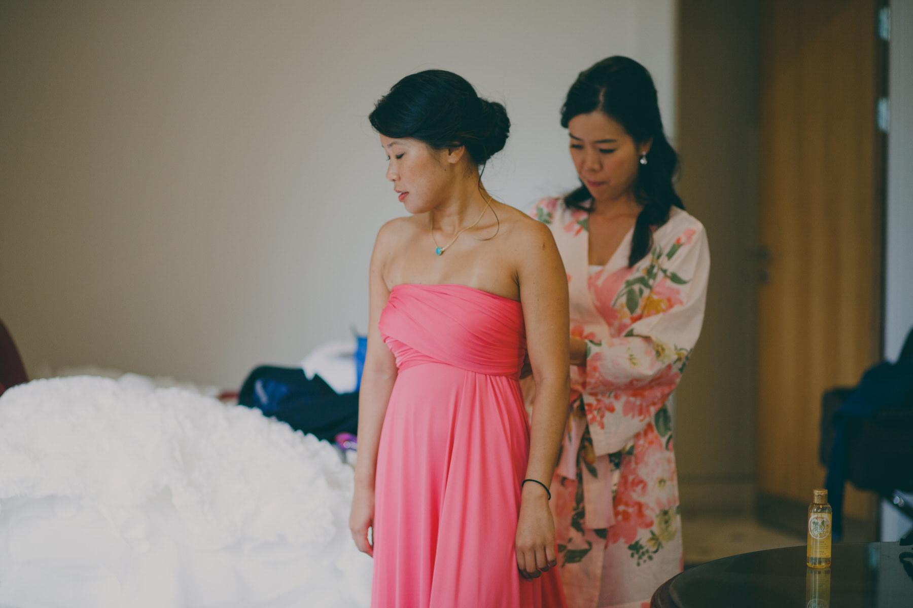 55 bride helping bridesmaid hot pink dress.jpg