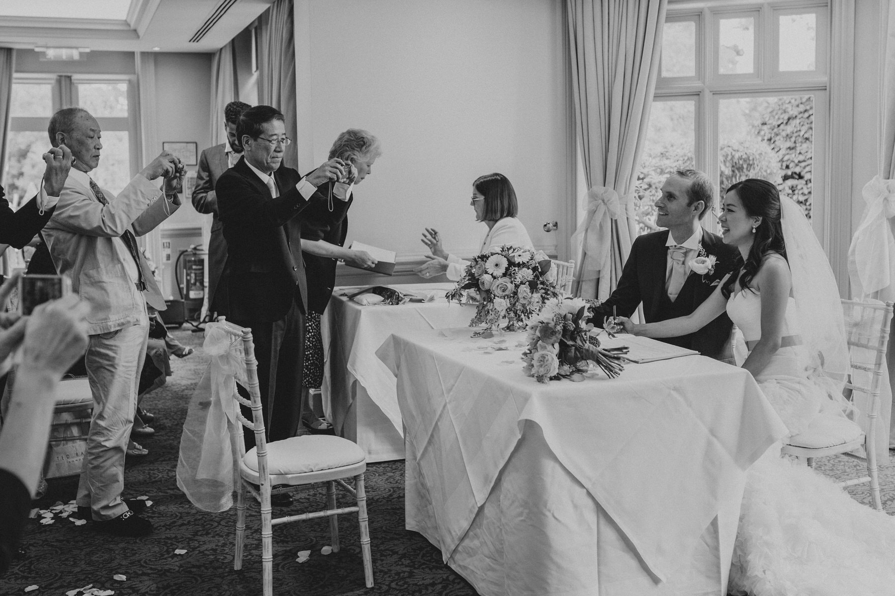 208 wedding guests photographing newly married couple.jpg